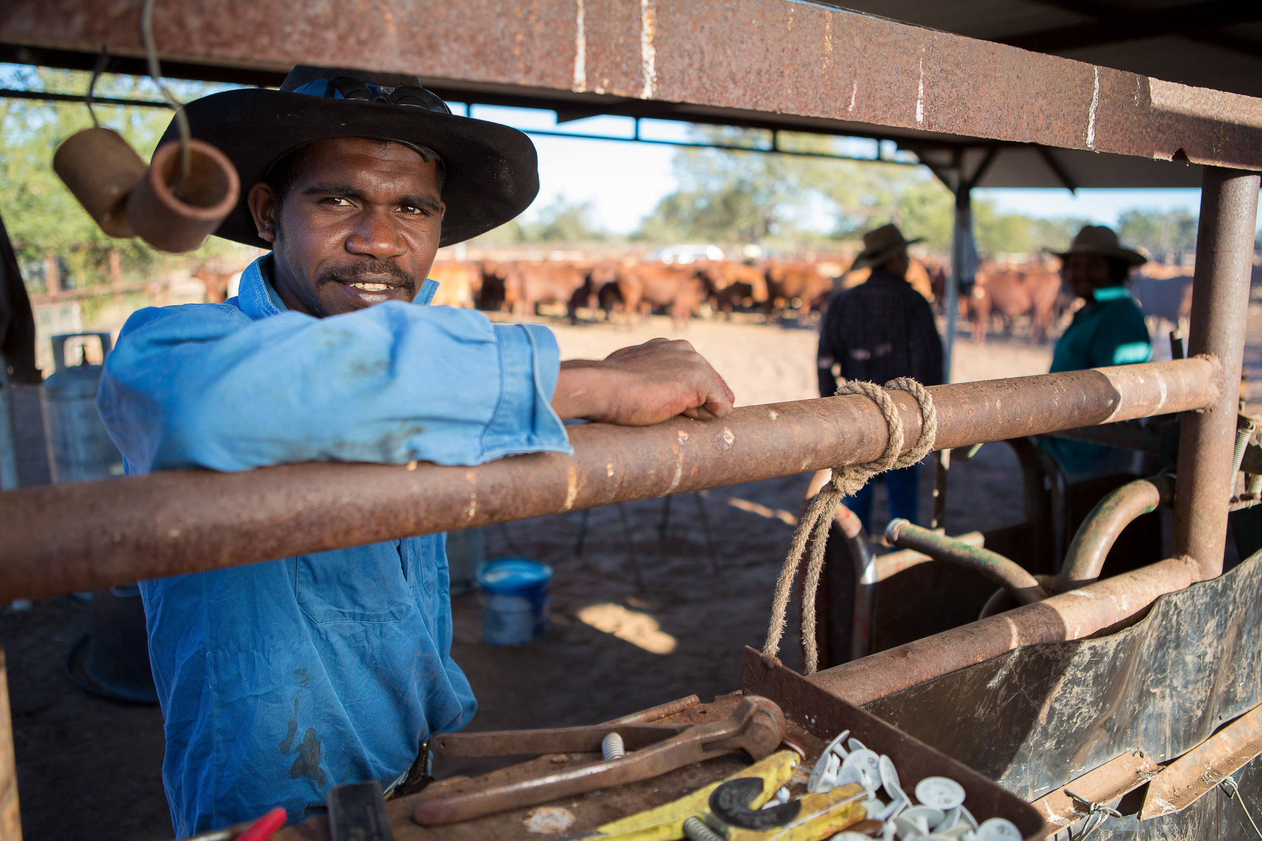 Indigenous Australian farm worker portrait on a cattle ranch leaning against the fence