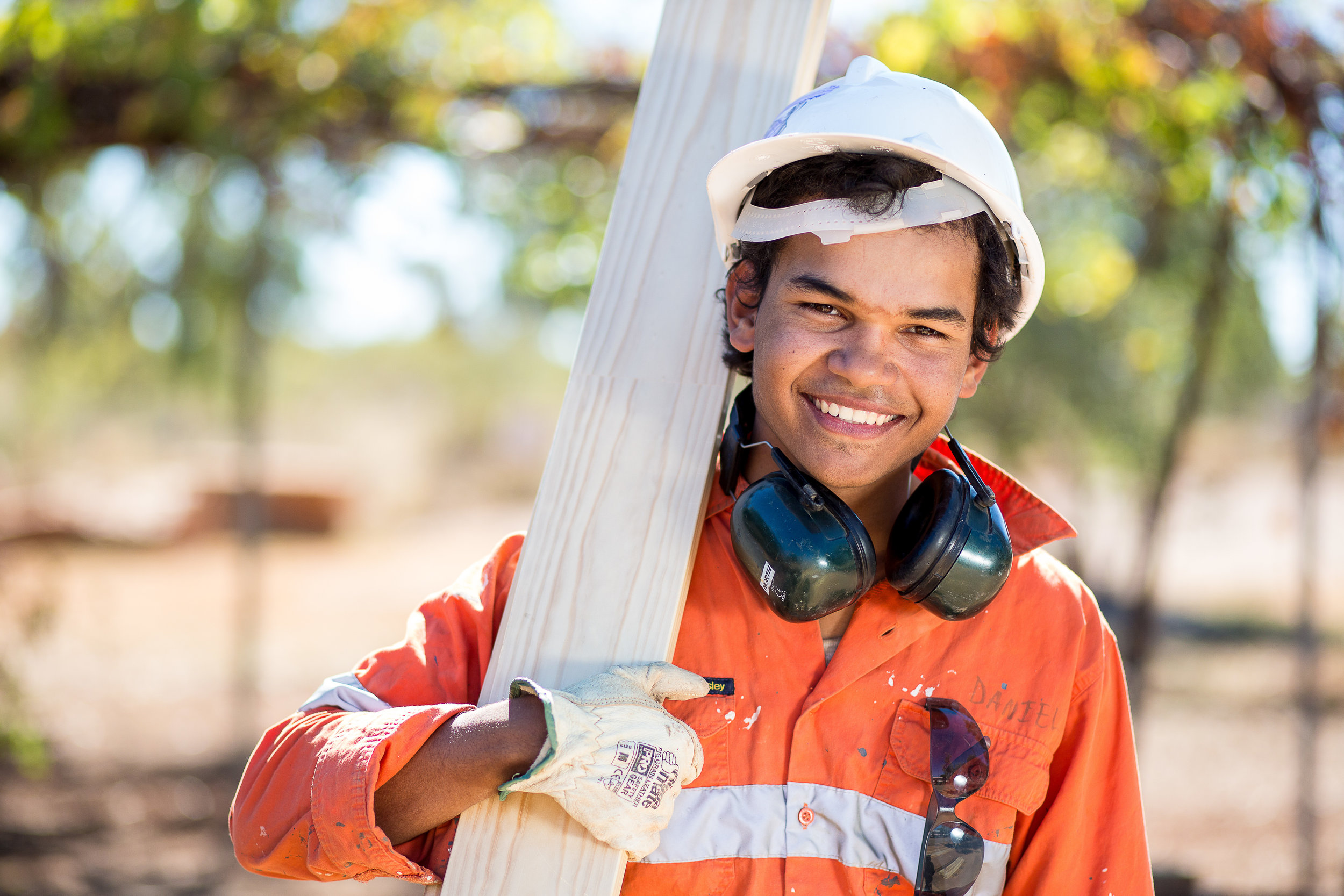 Indigenous Australian construction worker portrait showing young man wearing construction industry safety gear and holding wood