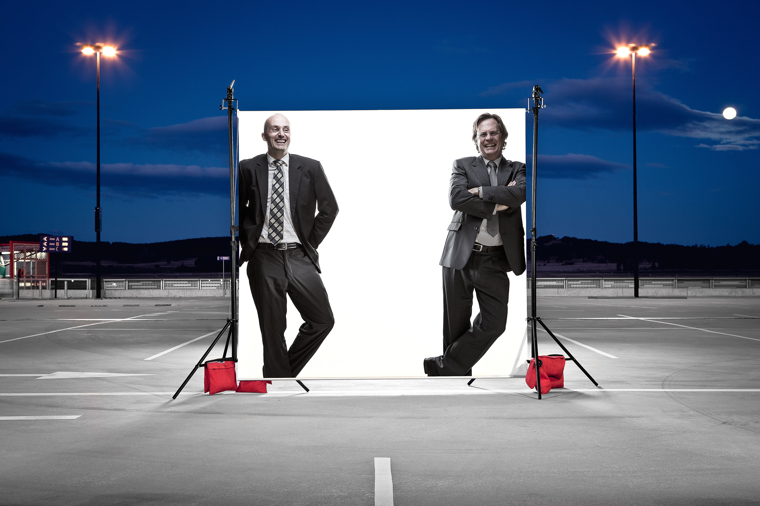 Business or trade magazine photograph showing two men framed within a photographic white background in an urban environment