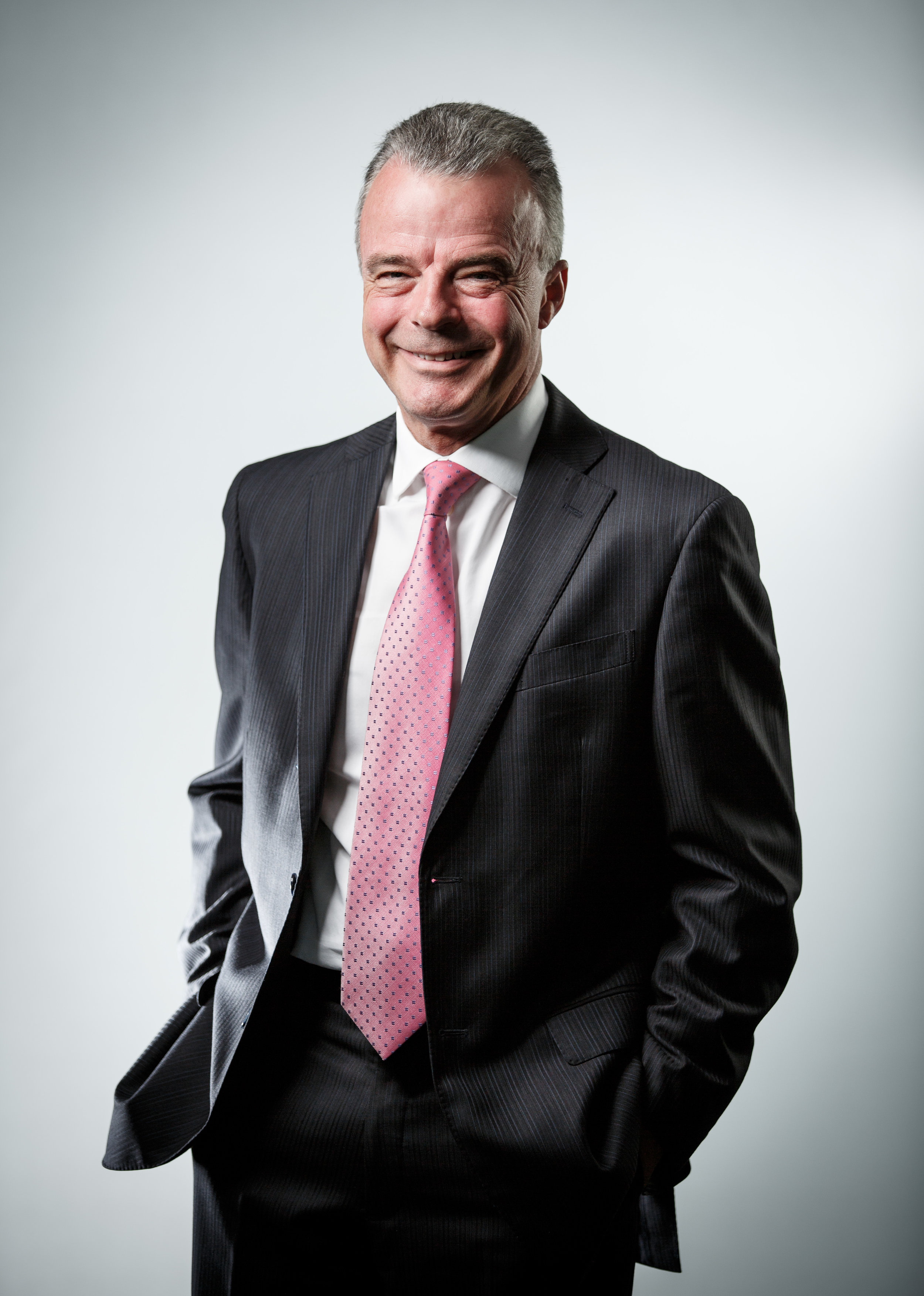 Brendan Nelson portrait photograph wearing a suite and smiling at camera with pink tie