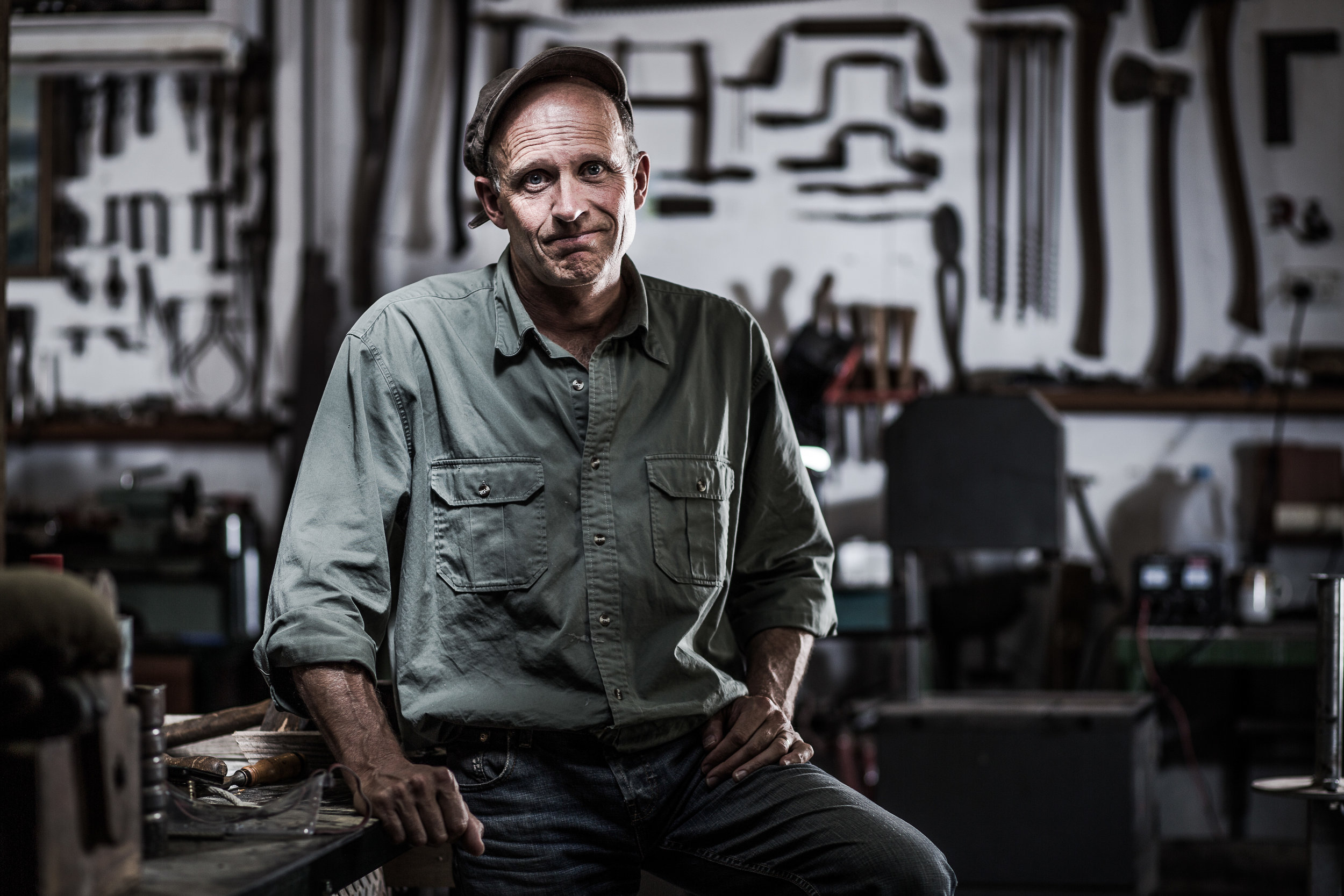 Workshop portrait of a man wearing jeans and a shirt looking frustrated