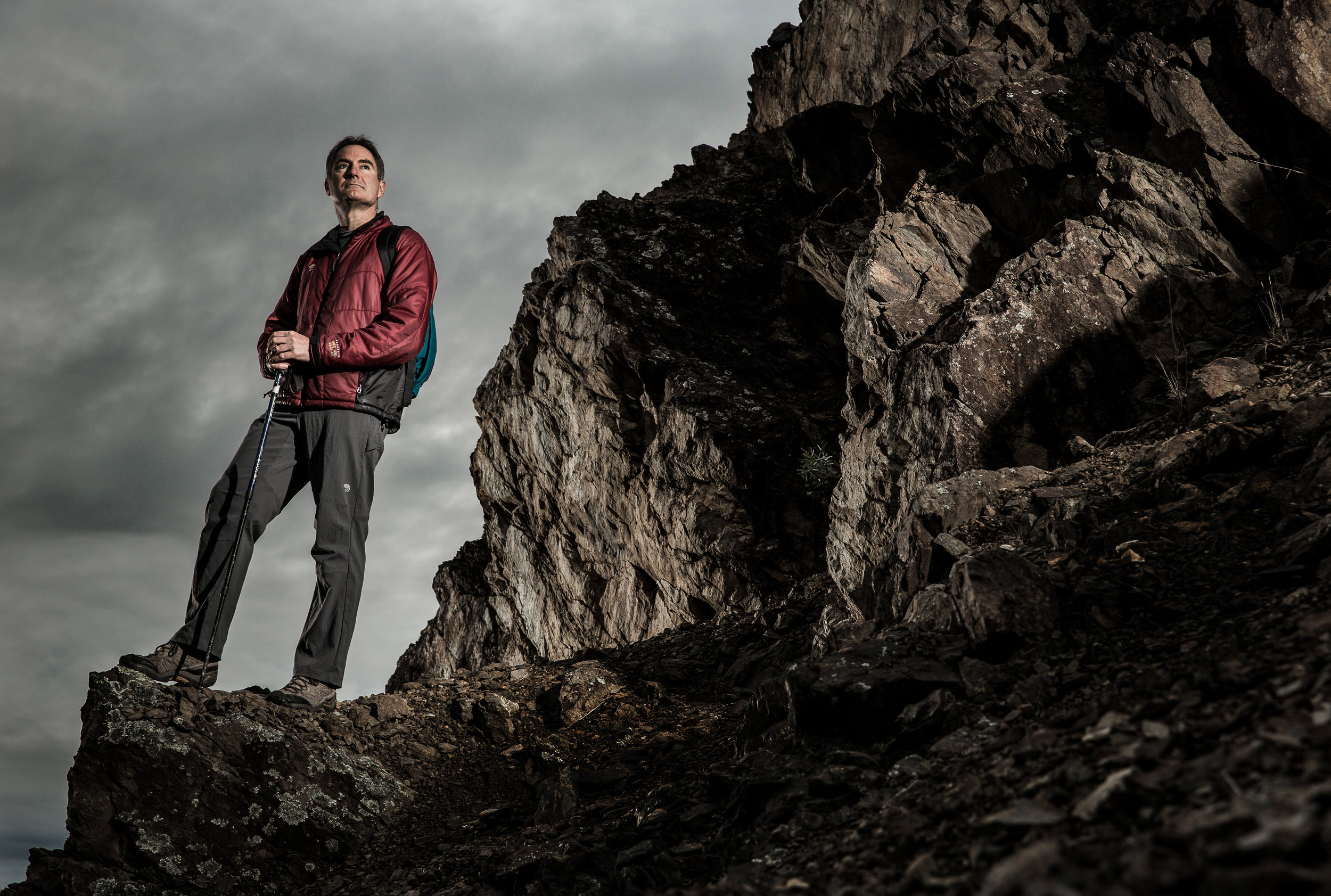 Environmental portrait  of Mountaineer Andrew Lock on a rock face wearing hiking clothes.