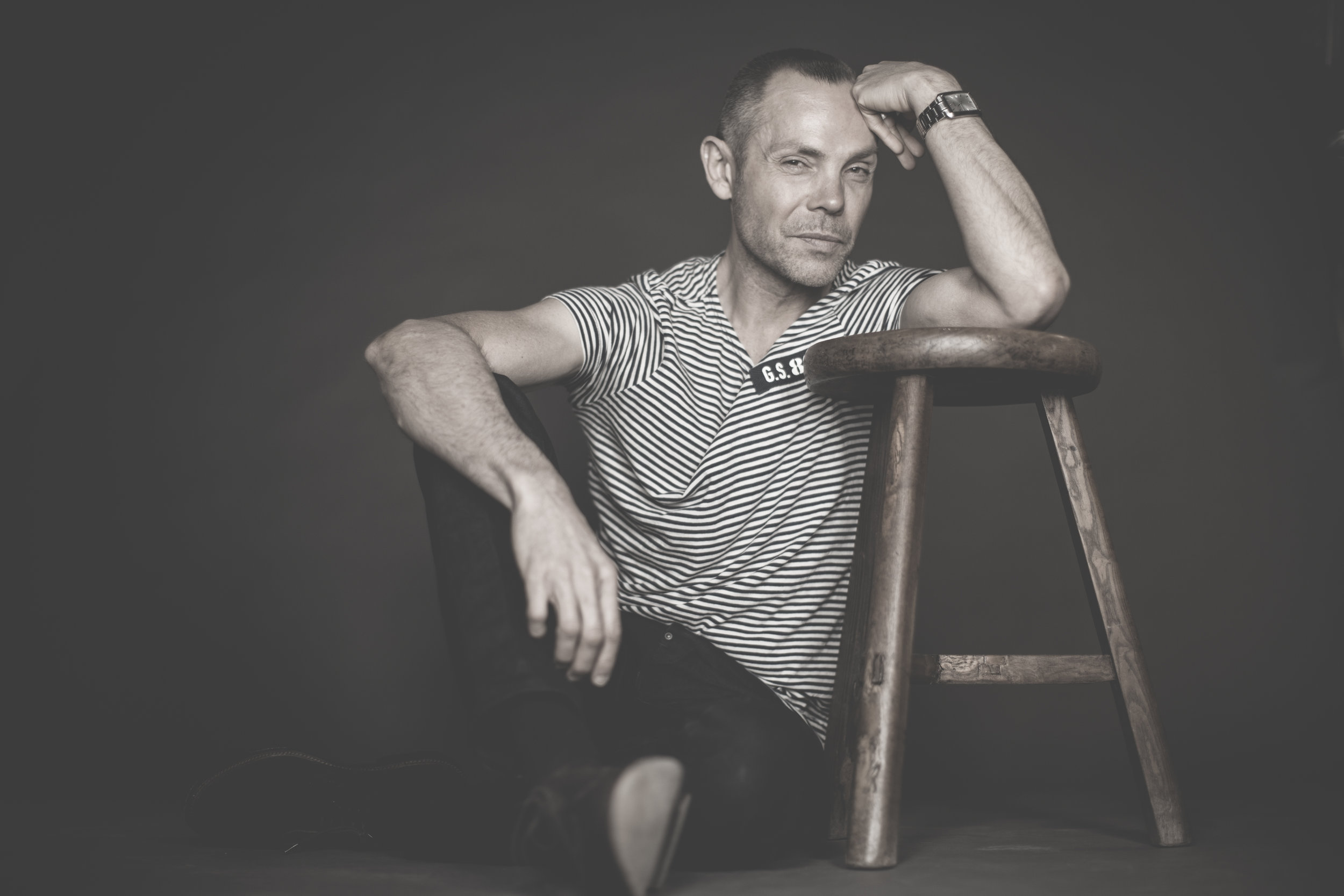Bison Homes design business owner Brian Tunks poses for a portrait with a wooden stool white strip tshirt relaxed portrait in studio