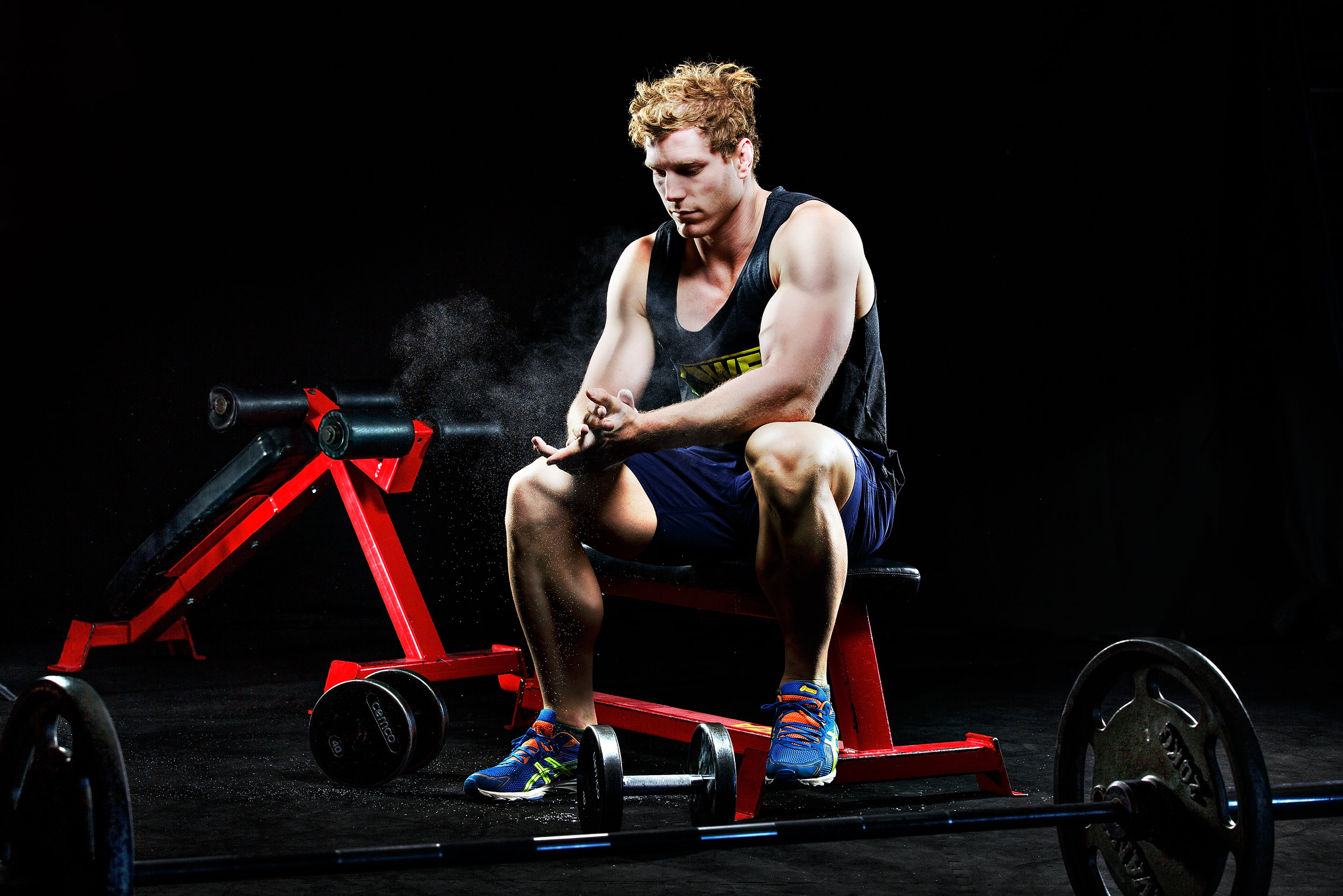 Rugby player David Pocock poses in the gym for a strong athlete style editorial portrait.