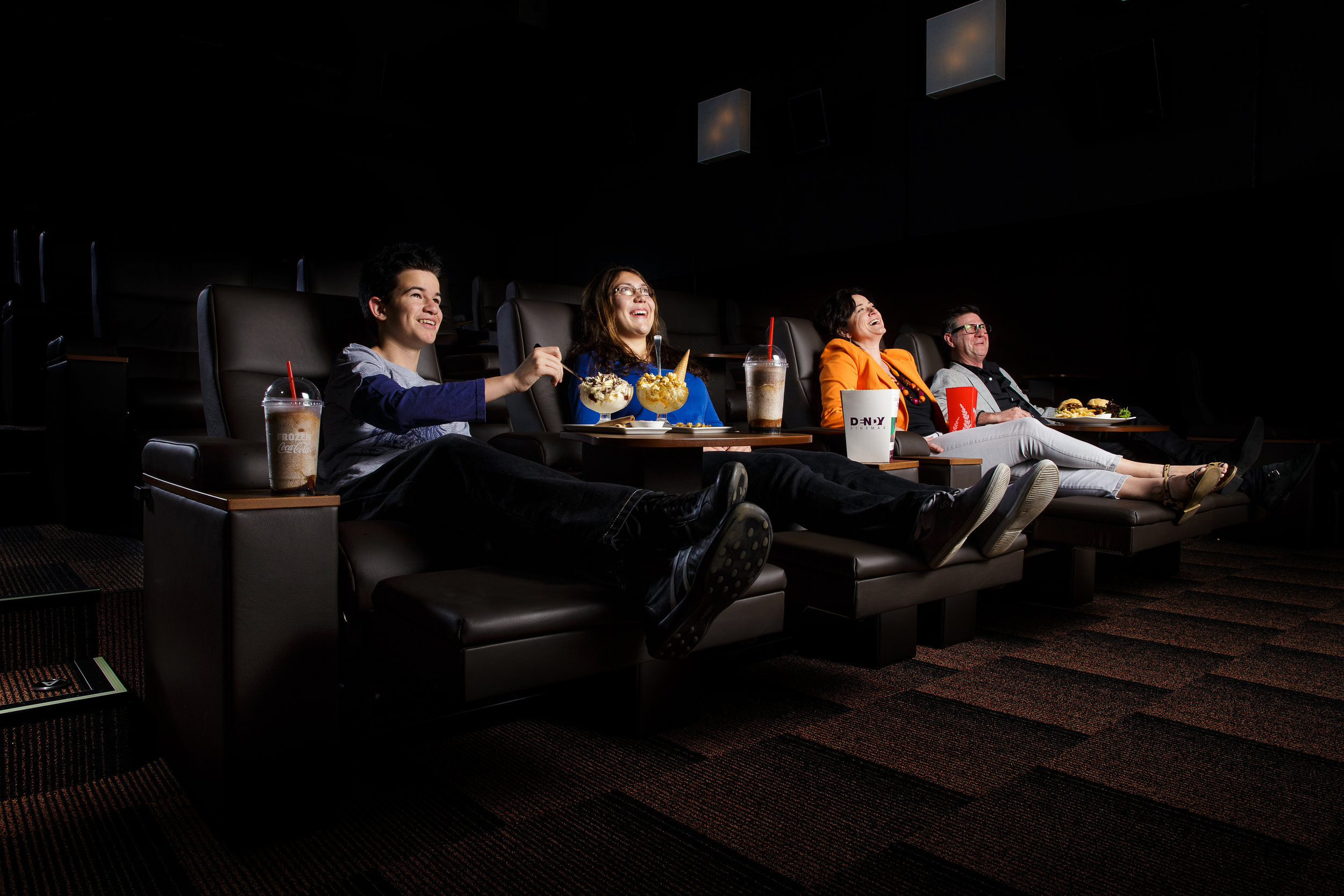 Premium cinema seating leather chairs and fine food with family enjoying a movie