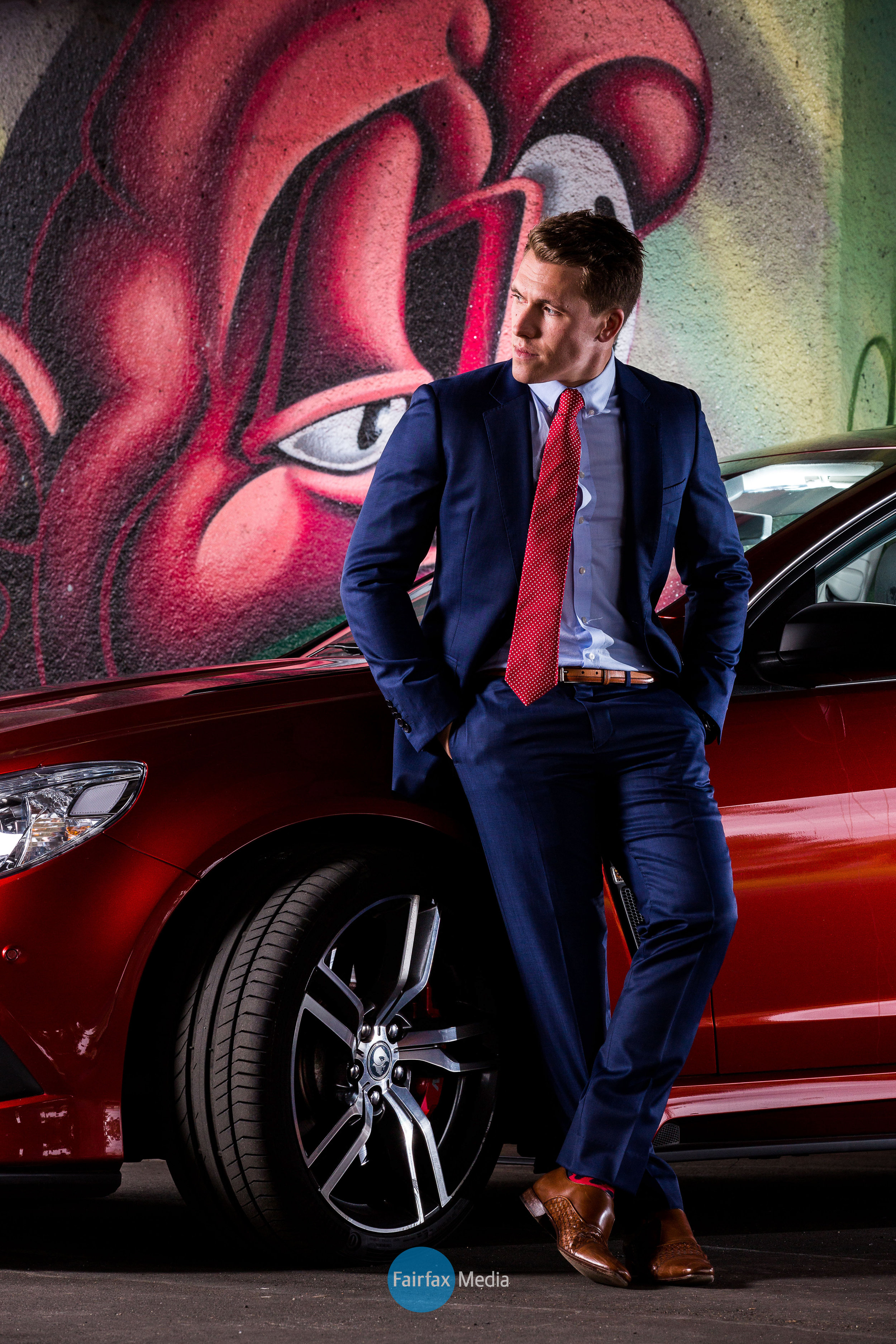 Colorful male fashion image of man in suite leaning against a red sports car with graffiti wall behind him