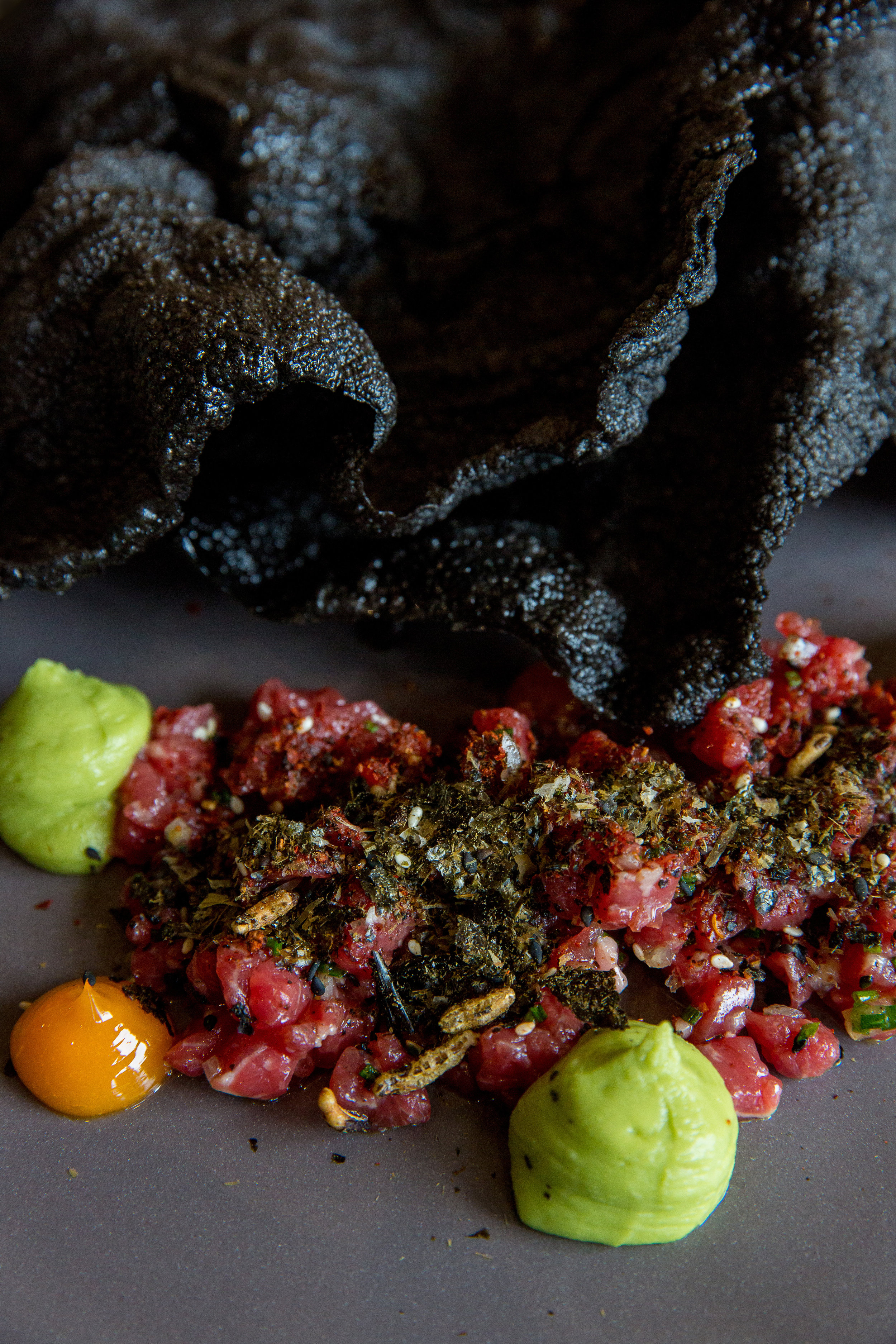 magazine editorial food photography of Boxgum Grazing beef tartare with miso cured egg yolk, avocado, fresh horseradish and crisp black rice, and yabbie jaffle