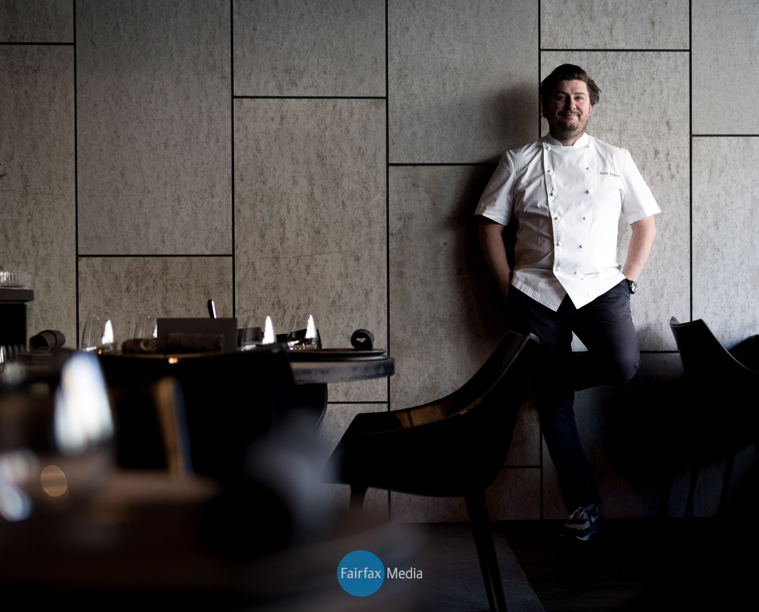 Portrait of famous chef Scott Pickett in his restaurant wearing chef whites and leaning against the wall