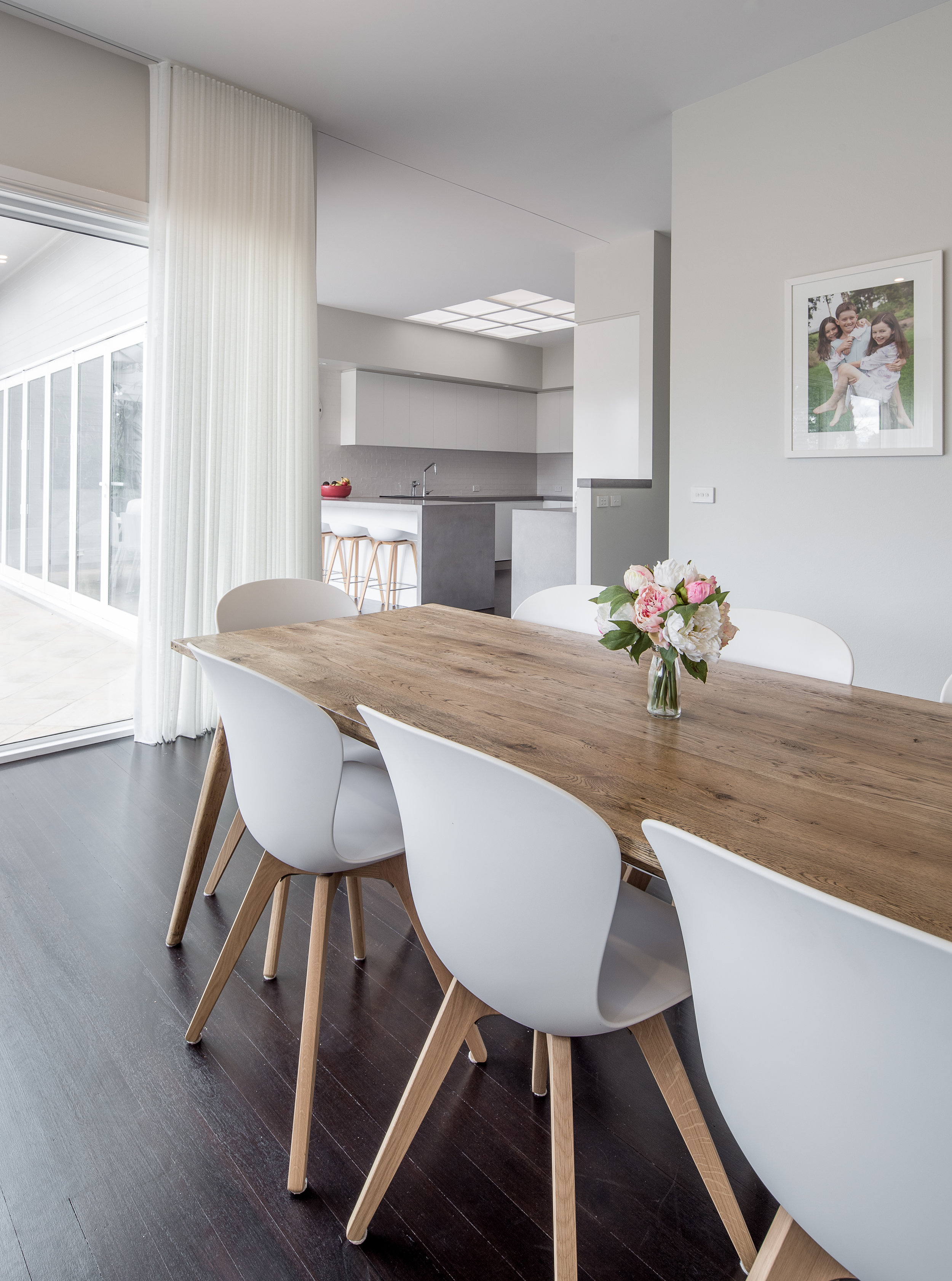 Family dining area in modern upper market home with timber dining table and matching chairs in white