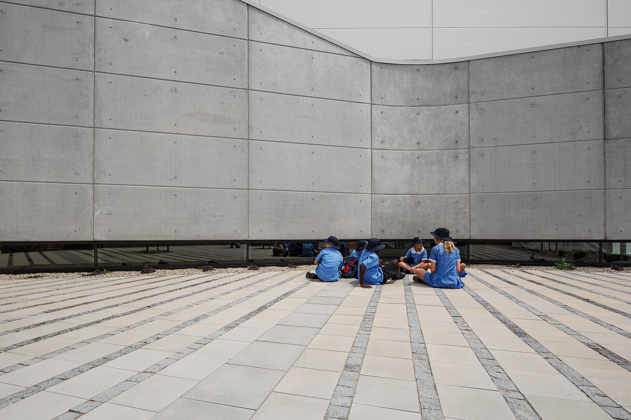 architectural school building in off form concrete curved wall with students sitting on the paving having lunch