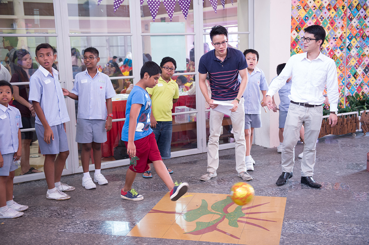 """Keng Leong (middle) and Ivan (right) coaching the students the techniques to achieve the perfect """"banana kick""""."""
