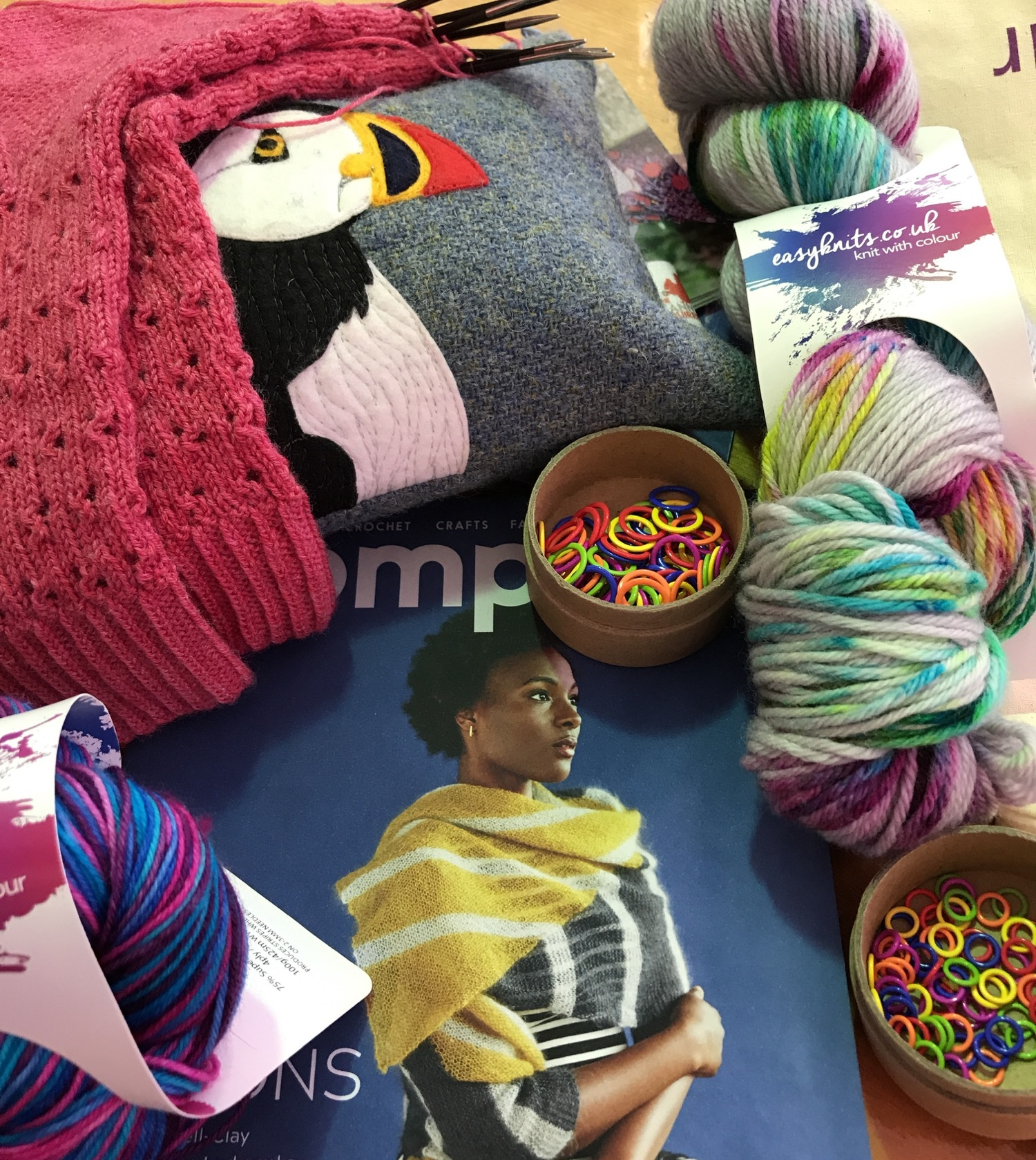 Clockwise starting at top left: My Antirrhinum socks in progress, sitting on my Canny Squirrel Puffin project bag (not purchased at the show). EasyKnits Dusted Dreams DK in Rio on Gris colourway. Cocoknits stitch markers in small and standard sizes, purchased from A Yarn Story. A copy of PomPom magazine for a friend. EasyKnits Gobstopper in the Killer Queen colourway for striped socks.