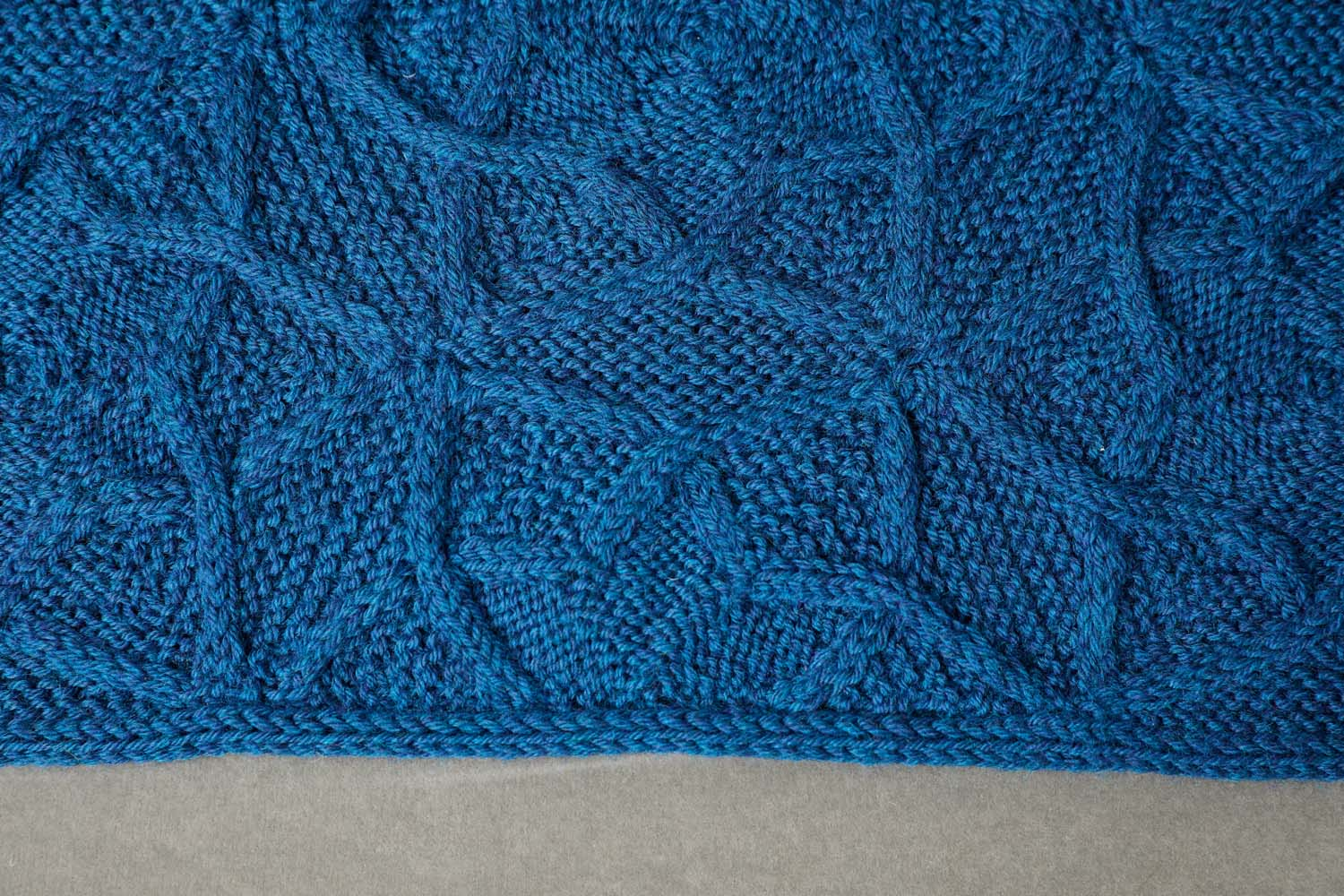 The half-hexagons at the edges are knitted on to the assembled blanket or cowl. Image © Jesse Wild.