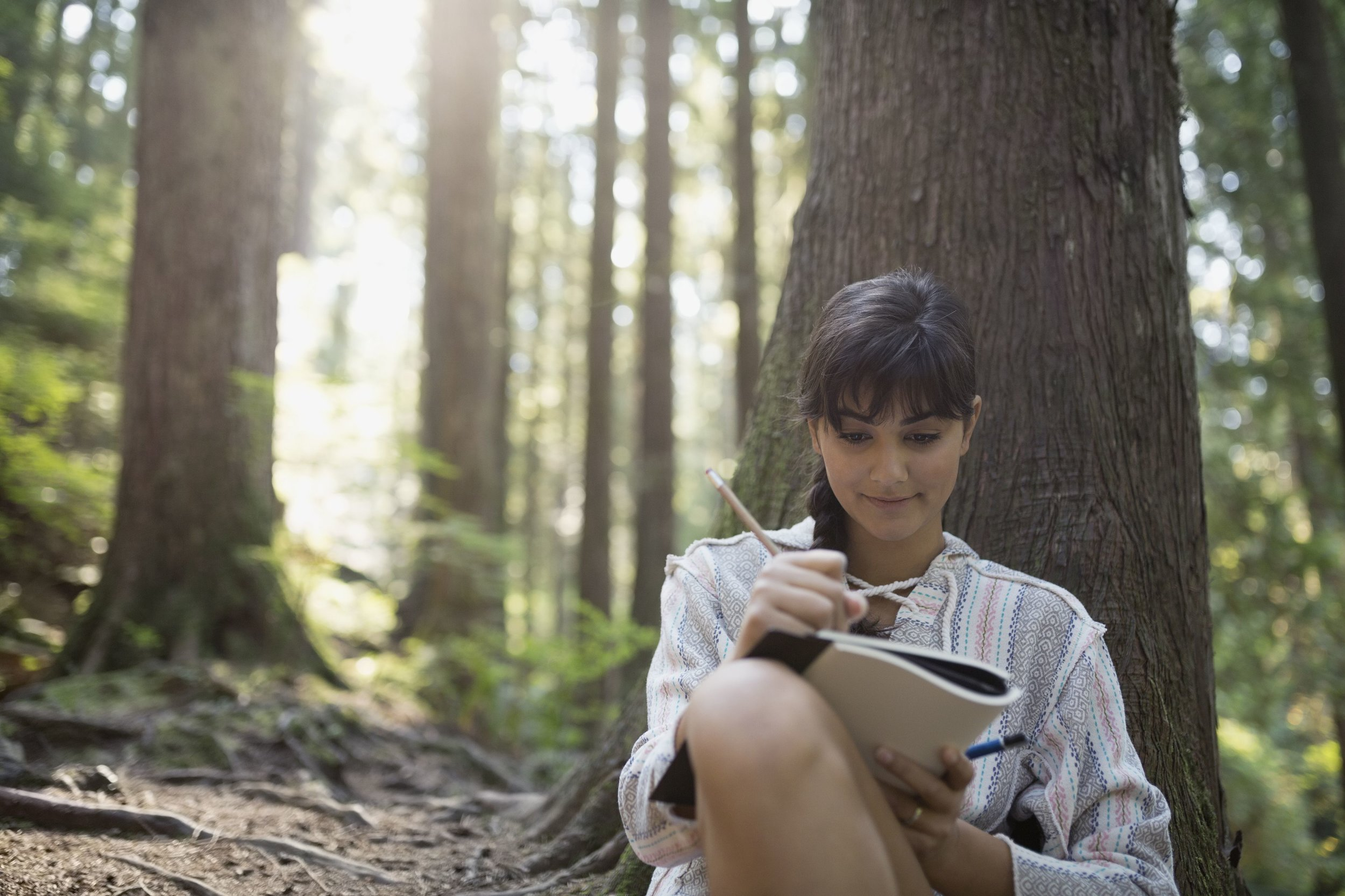 woman-writing-in-journal-against-tree-in-woods-522795579-5917477c5f9b5864703219cb.jpg