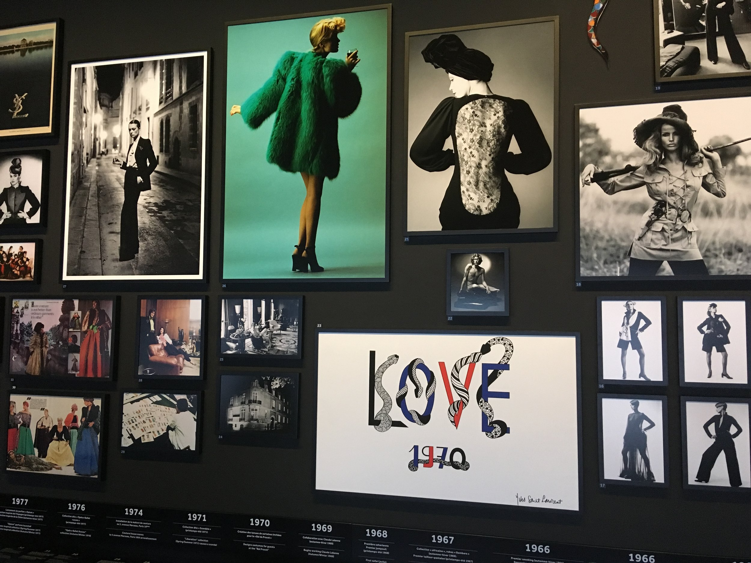 Helmut Newton's iconic image of YSL's Le Smoking, shot in rue Aubriot, Paris, 1975, hanging alongside Jeanloup Sieff's 1970 image of a YSL lace-back dress