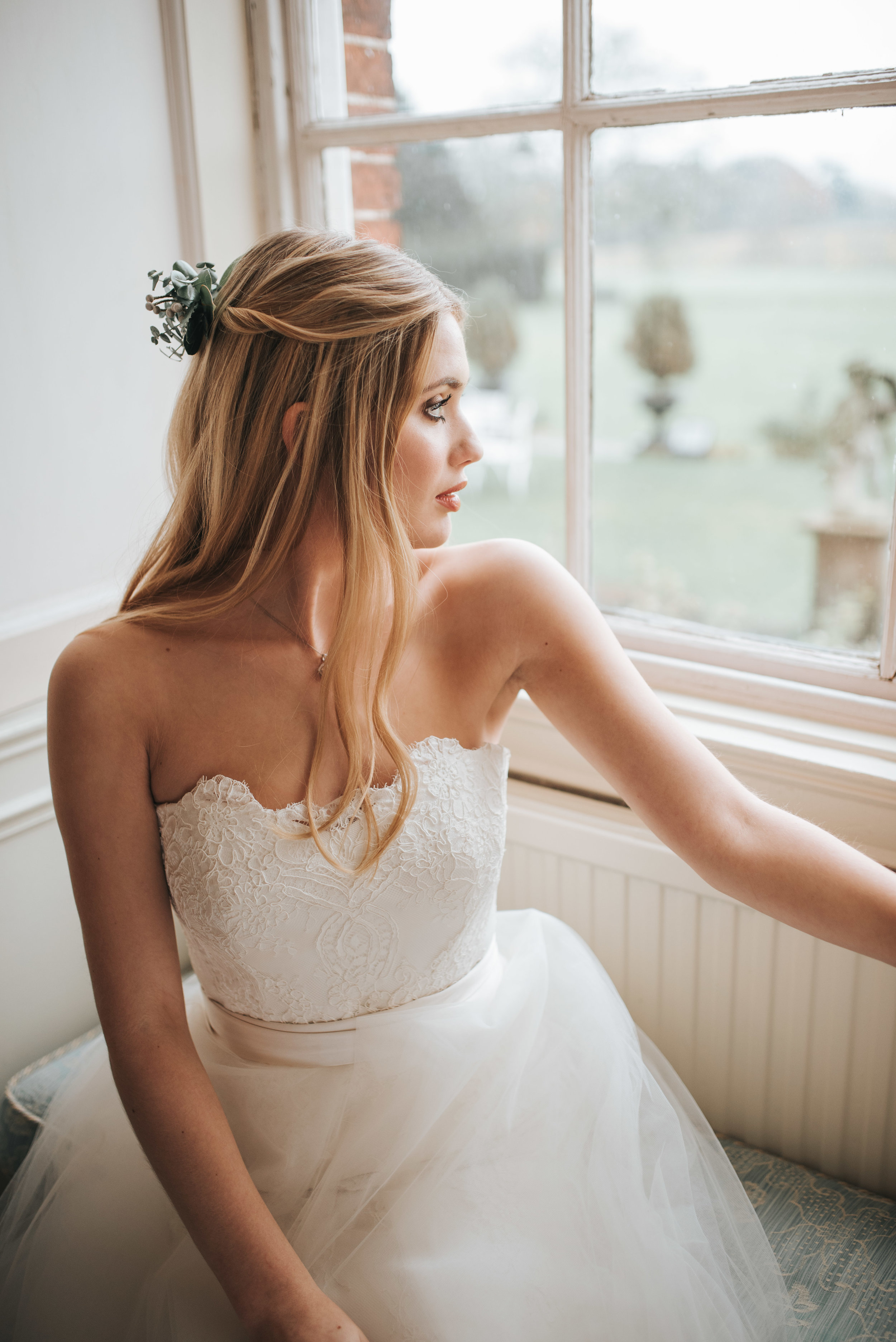 looking out of the window onto the lawns in white bridal gown.jpg