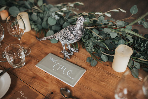 Table with invitations and green floral decor.jpg