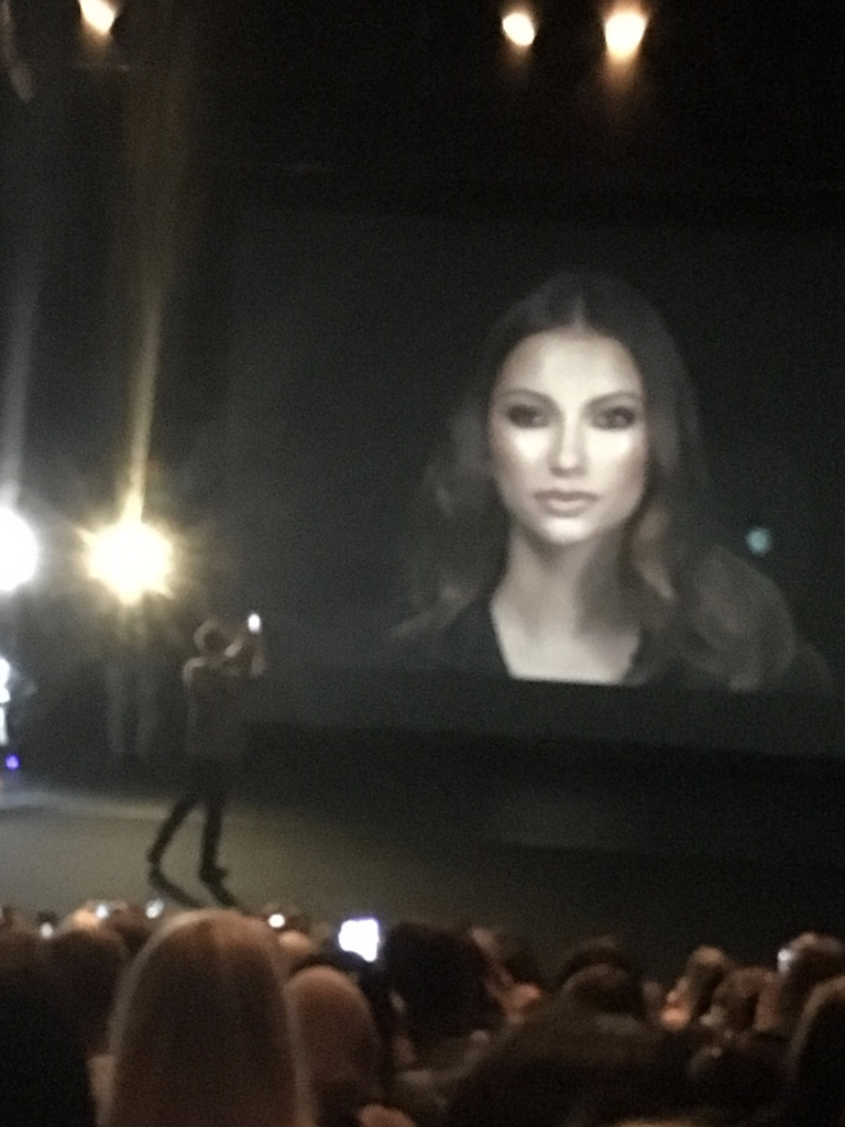 Mario on stage with the screen in the background