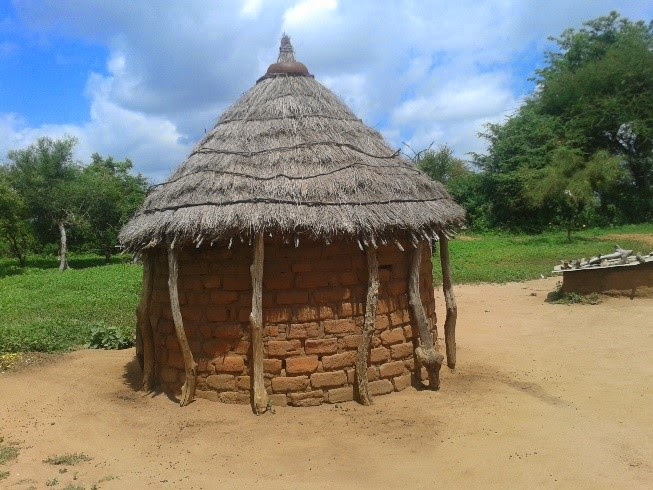 A home constructed of local bricks and a thatched roof.