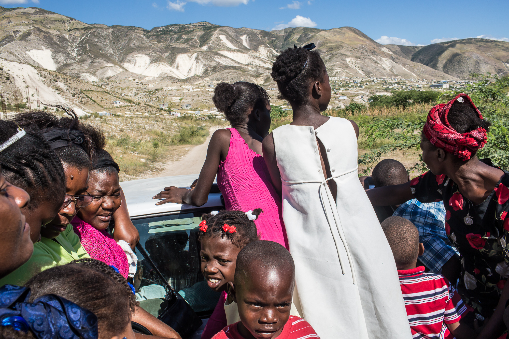 Worshipers catch a ride to their homes in the back of a pickup truck following services at Church of God for Fighting Pentecostal Church on the edge of the Corail-Cesselesse camp for people displaced by the 2010 earthquake on Sunday, December 21, 2014 in Port-au-Prince, Haiti. The camp and surrounding areas are home to tens of thousands of people, many of whom live in makeshift shacks in a barren landscape with little or no access to jobs or resources.