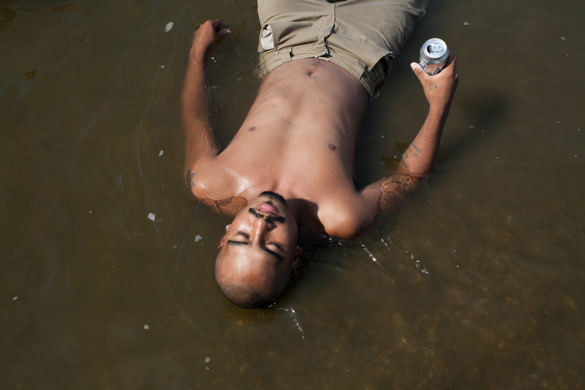 "Alazar ""Junior"" Soto lies in the Des Moines River while tubing on Sunday, July 15, 2012 in Lehigh, IA."