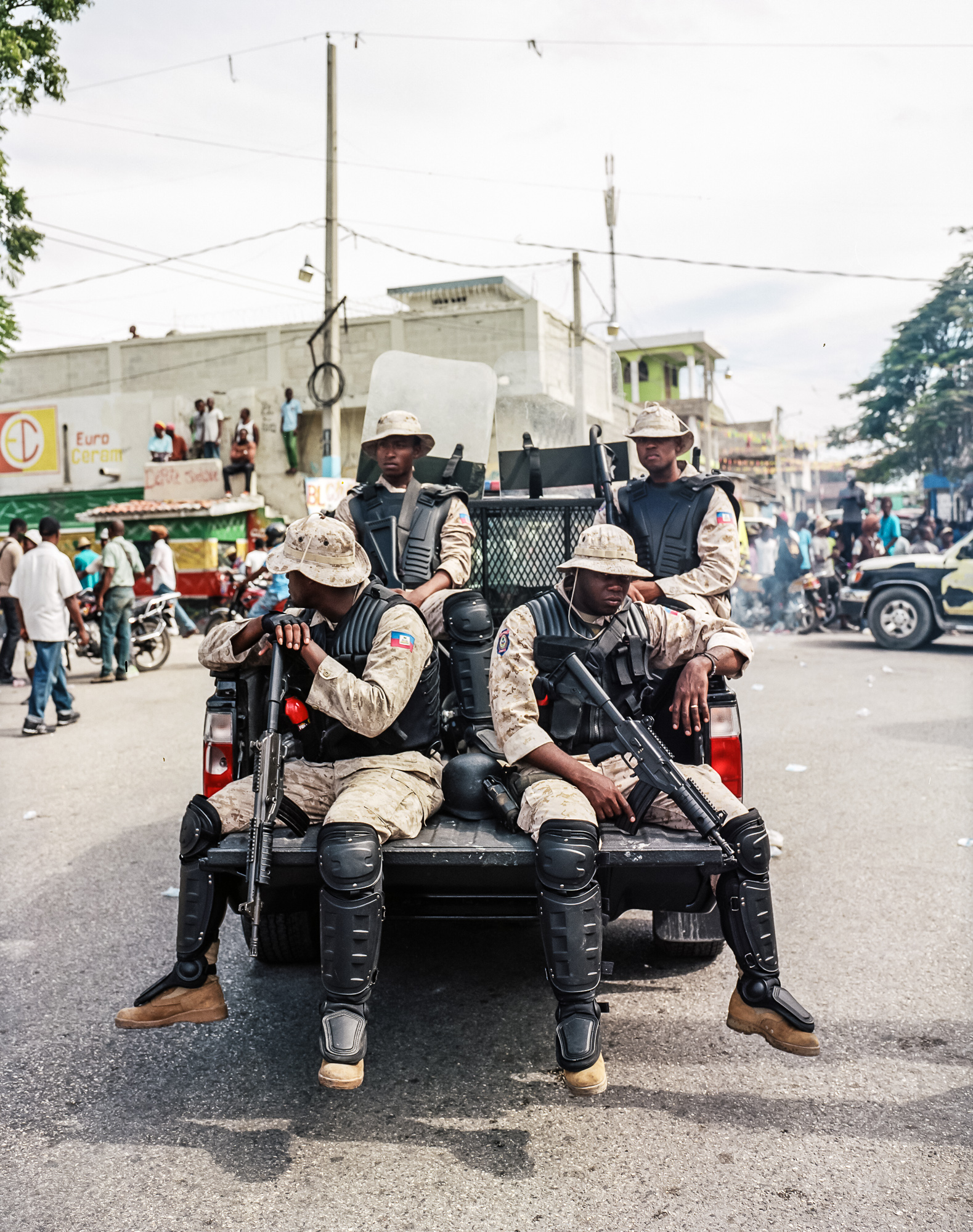Police keep watch from the back of a pickup truck during an anti-government protest on Tuesday, December 16, 2014 in Port-au-Prince, Haiti. President Michel Martelly was elected in 2010 with great hope for reforms, but in the wake of slow recovery and parliamentary elections that are three years overdue, his popularity has suffered tremendously, forcing Prime Minister Laurent Lamothe to resign.