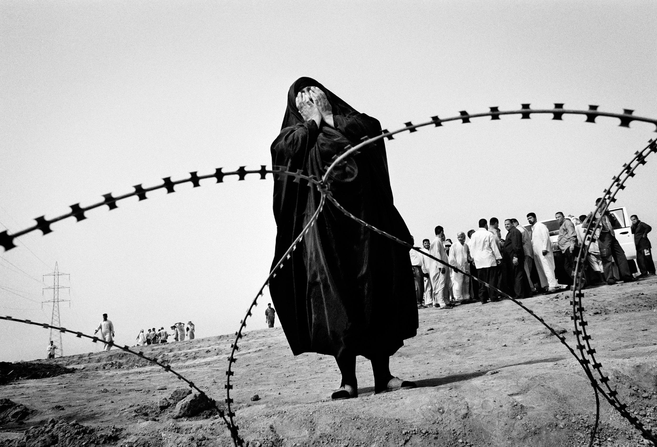2003, General News Reportage, 3° premio © Dario Mitidieri/Getty Images Iraq.  Una donna presso una fossa comune vicino ad Al-Mahawil. Stando ai dati raccolti da centri di osservazione per i diritti umani, 30.000 persone scomparvero in Iraq durante il Regime di Saddam Hussein. Alcune sparirono negli anni Ottanta, quando Saddam ordinò l'arresto e l'esecuzione di migliaia di comunisti, musulmani sciiti e rivali interni al suo stesso partito