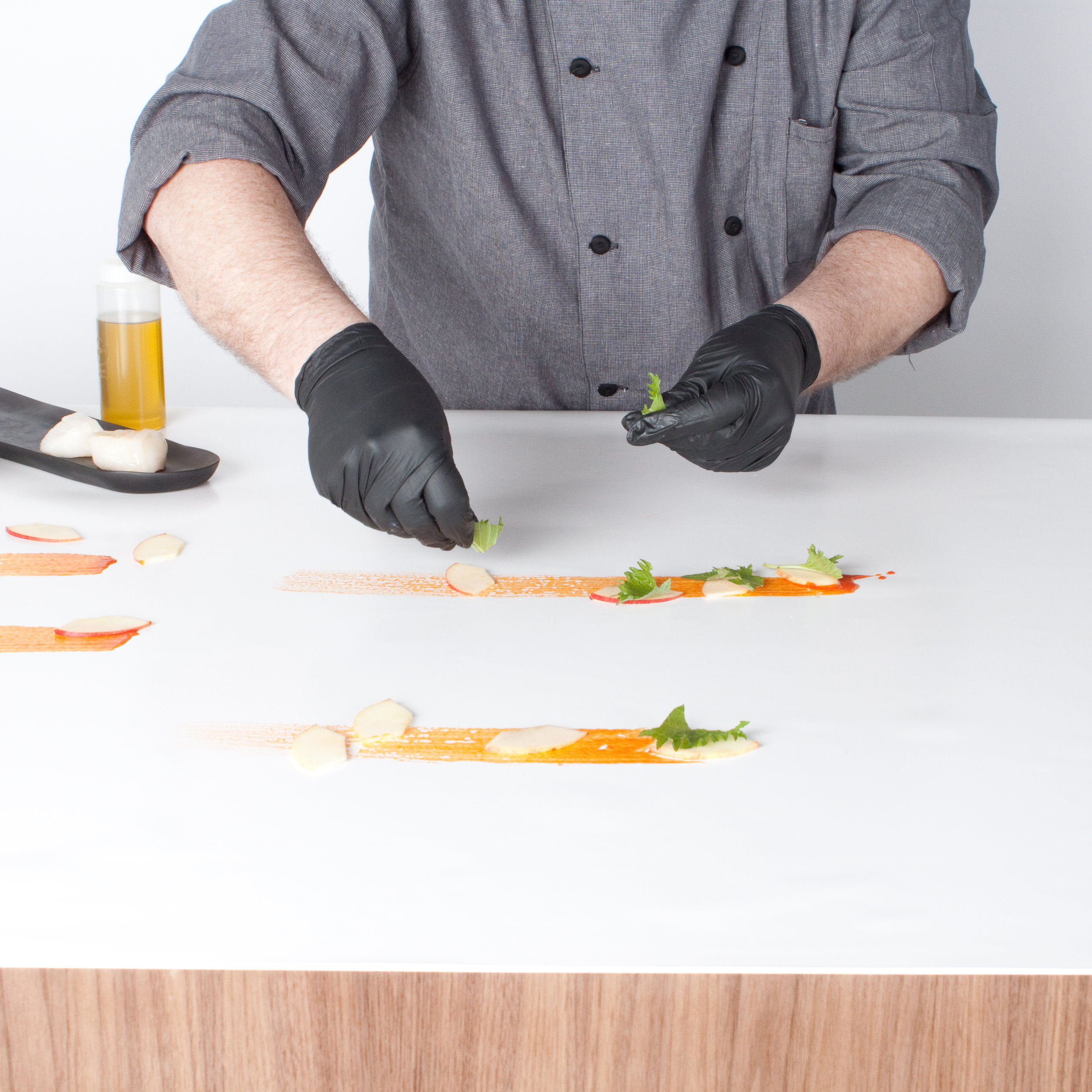chef's ta•ble   1. A quiet demo in which the chef assembles, seasons, slices and stacks bites of food live at an event, in full view of the guests.  2. An engaging presentation that brings the kitchen out to the party.