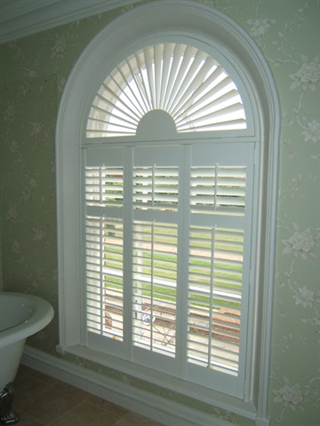 Wood shutter with sunburst arch and divider rail in cased window