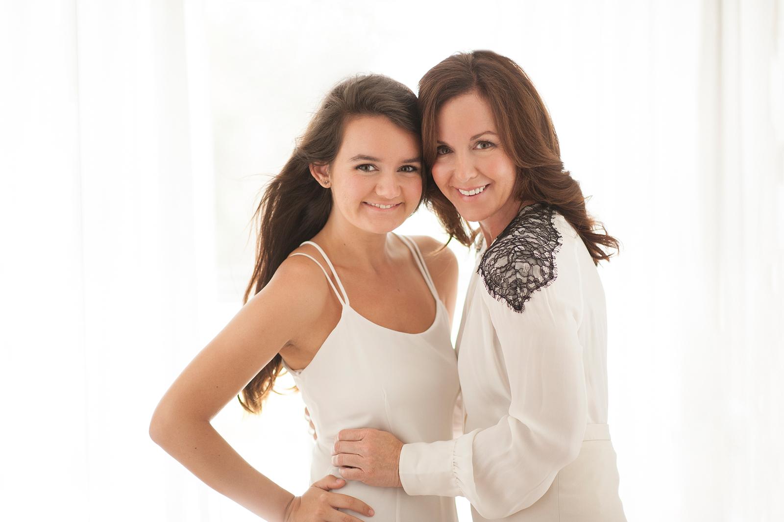 21-mother-daughter-backlit-smiling-standing-white-hands-hip.jpg