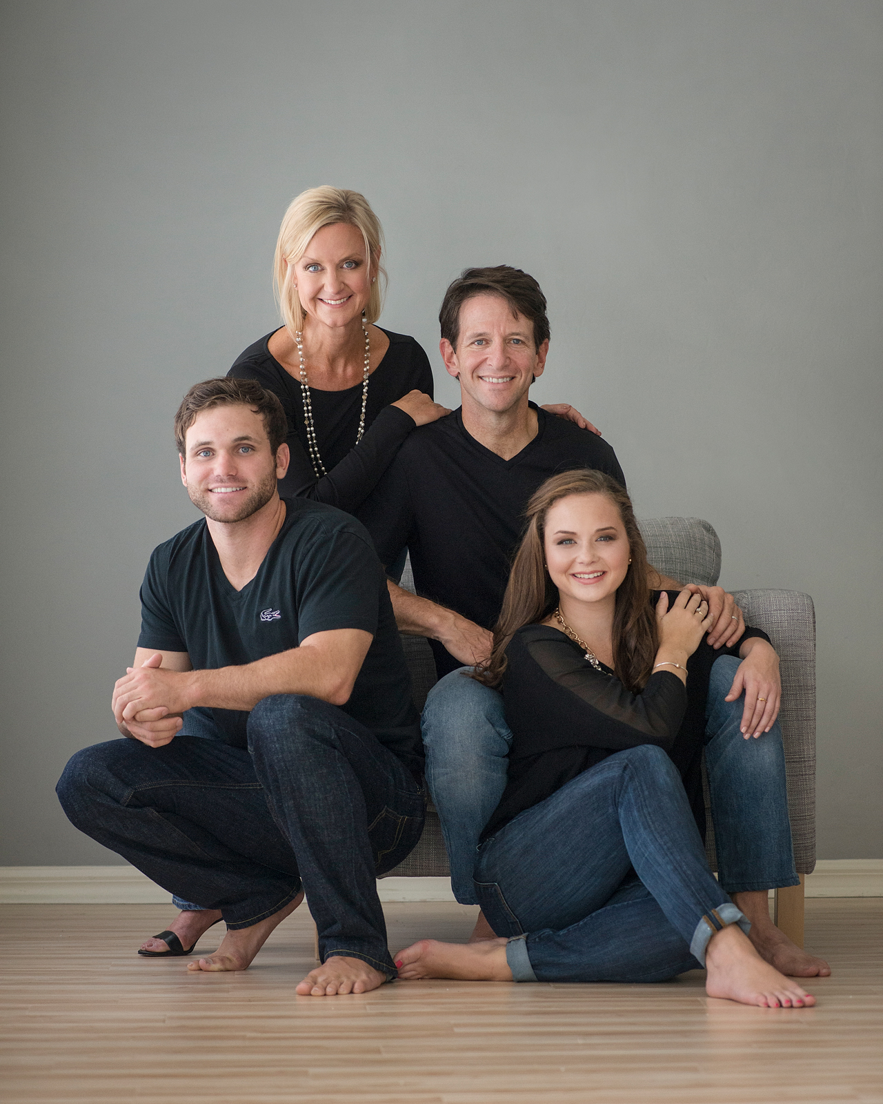 20-family-seated-pose-black-shirts-jeans-studio.jpg