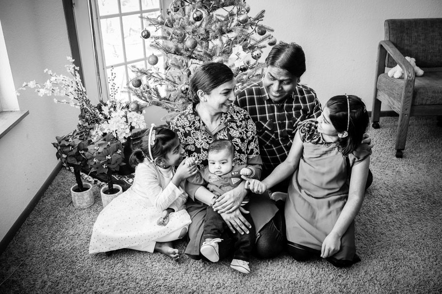 black and white family picture by Christmas tree
