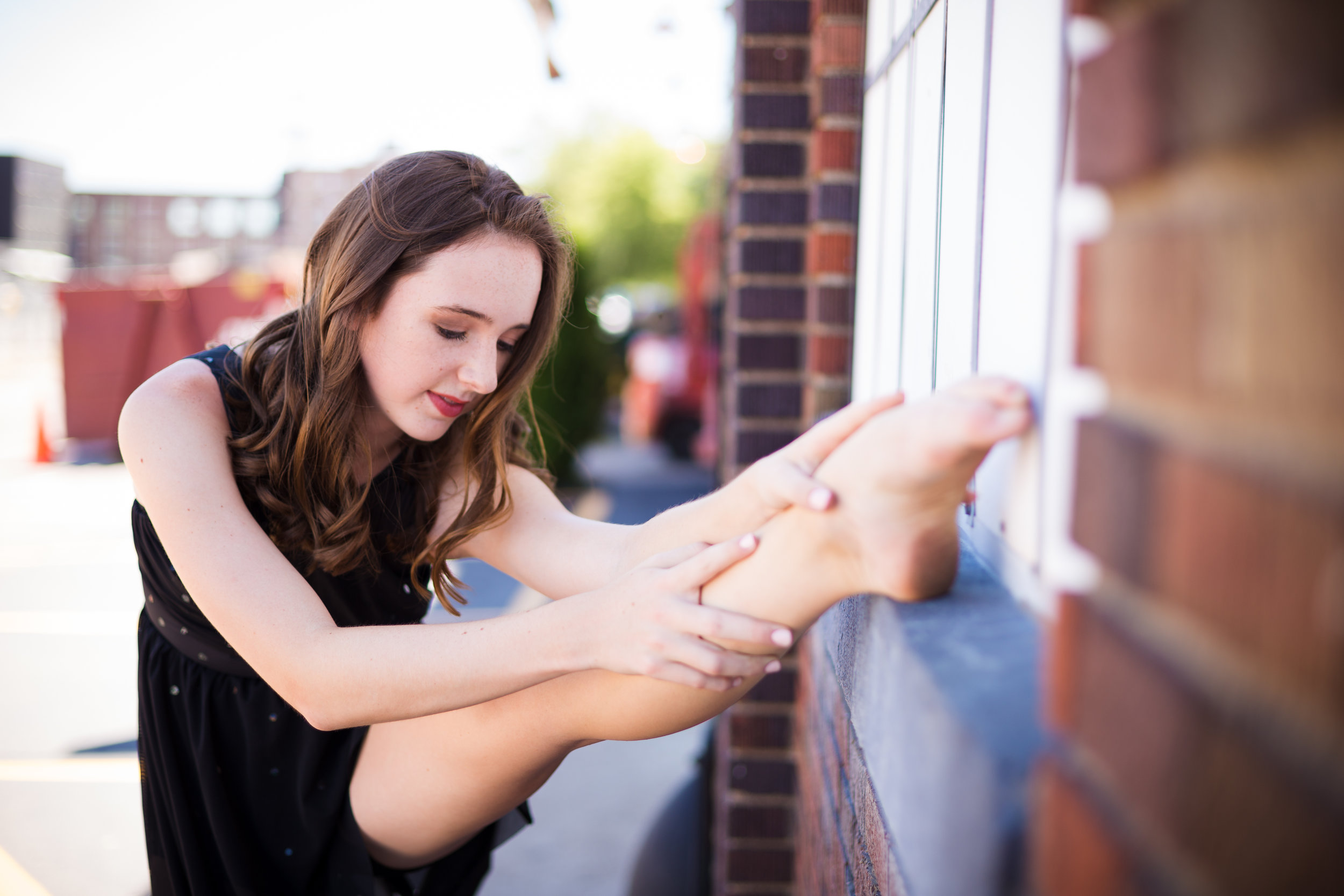 ballerina stretching on ledge of brick wall