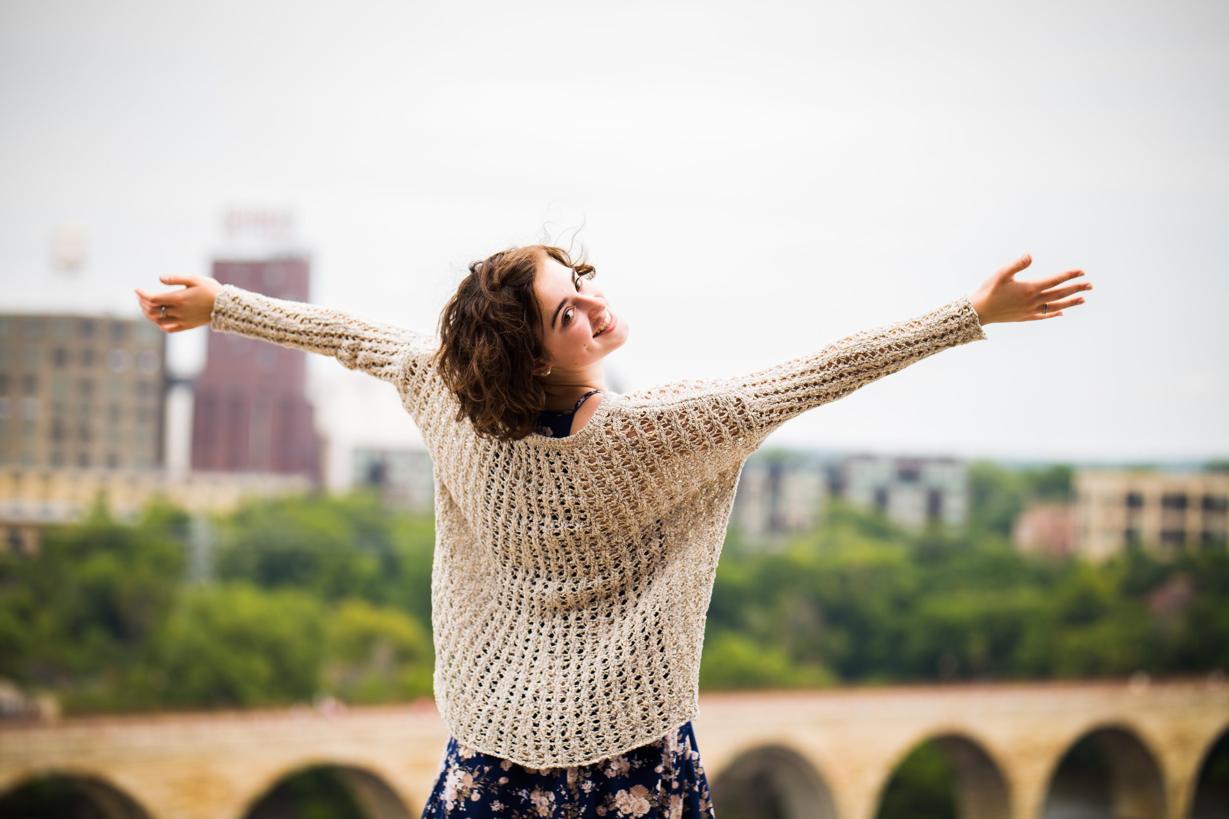 girl with outstretched arms in front of Stone Arch Bridge