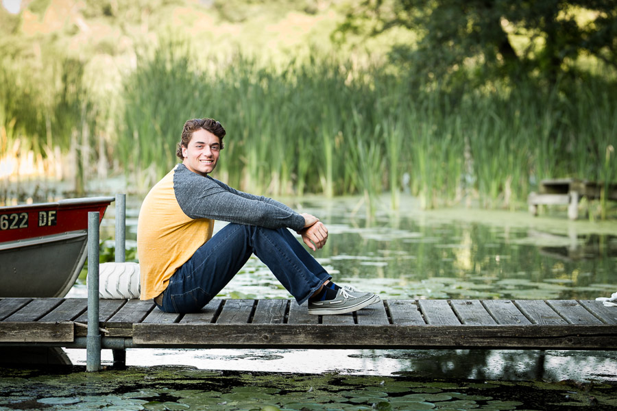 teenage boy sitting on dock next to lake - wayzata senior photos