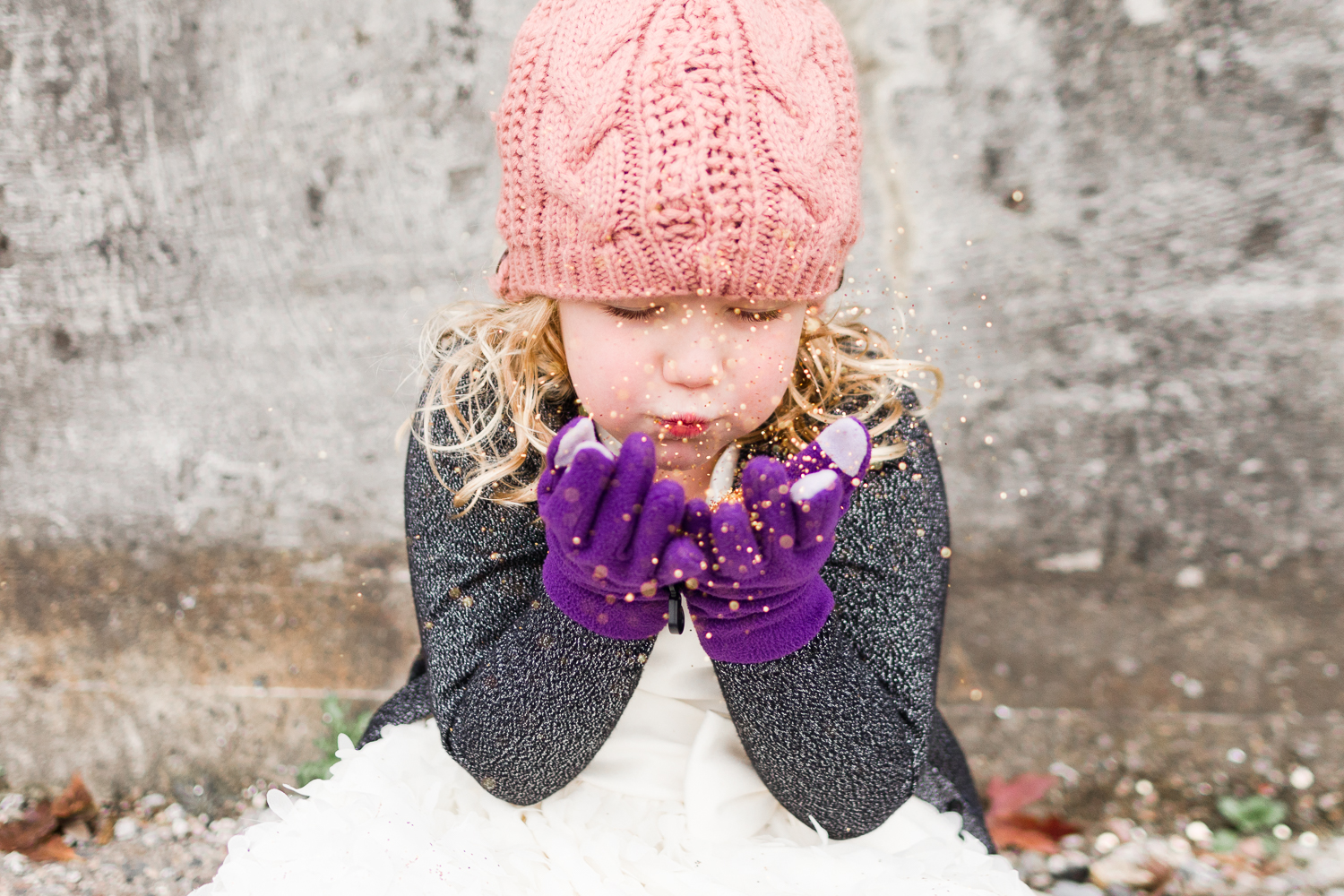 little girl in pink knit hat blowing golden glitter - child photographer twin cities