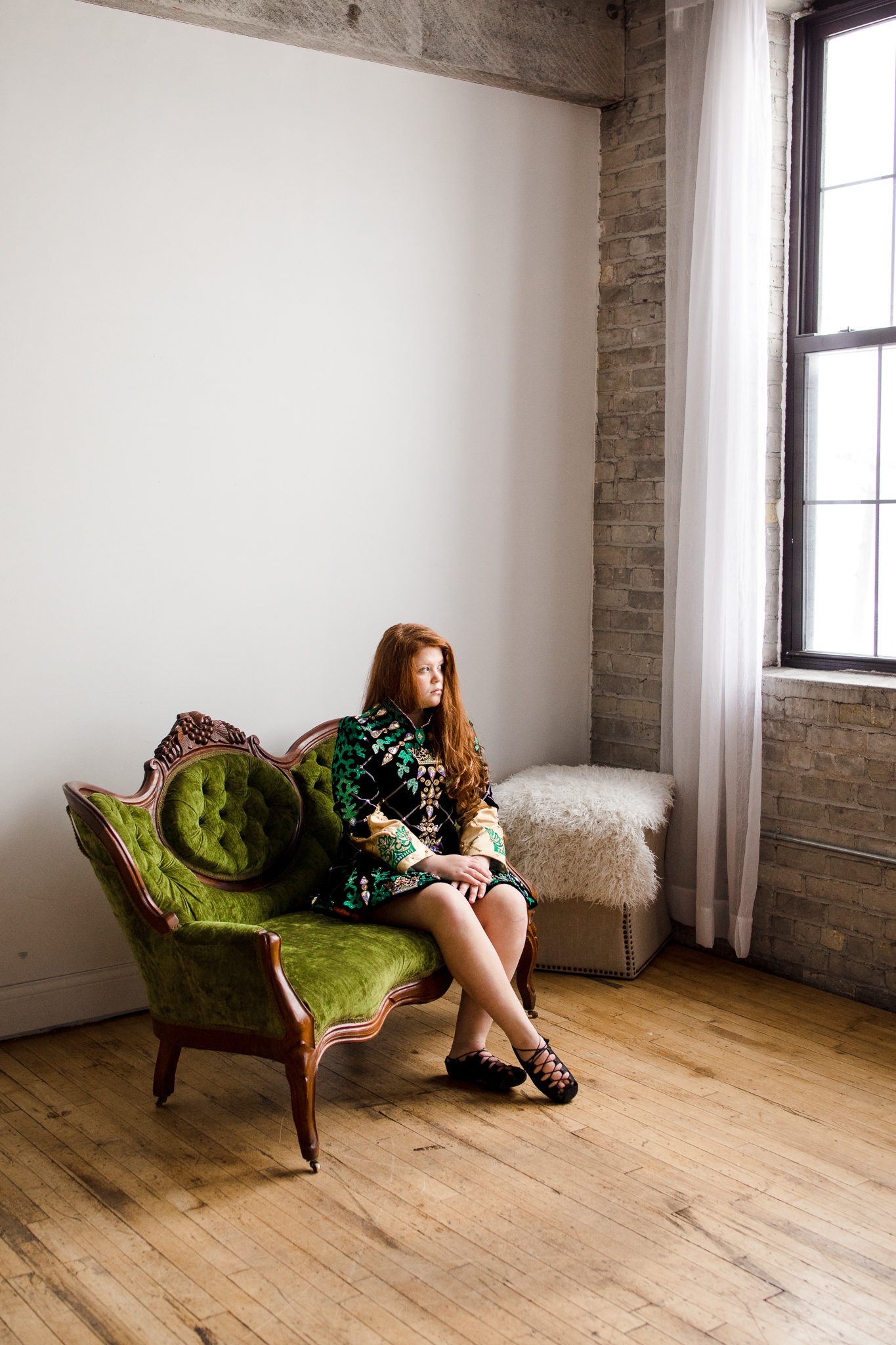 girl in green Irish dance dress sitting on green couch - Plymouth Lifestyle Photographer