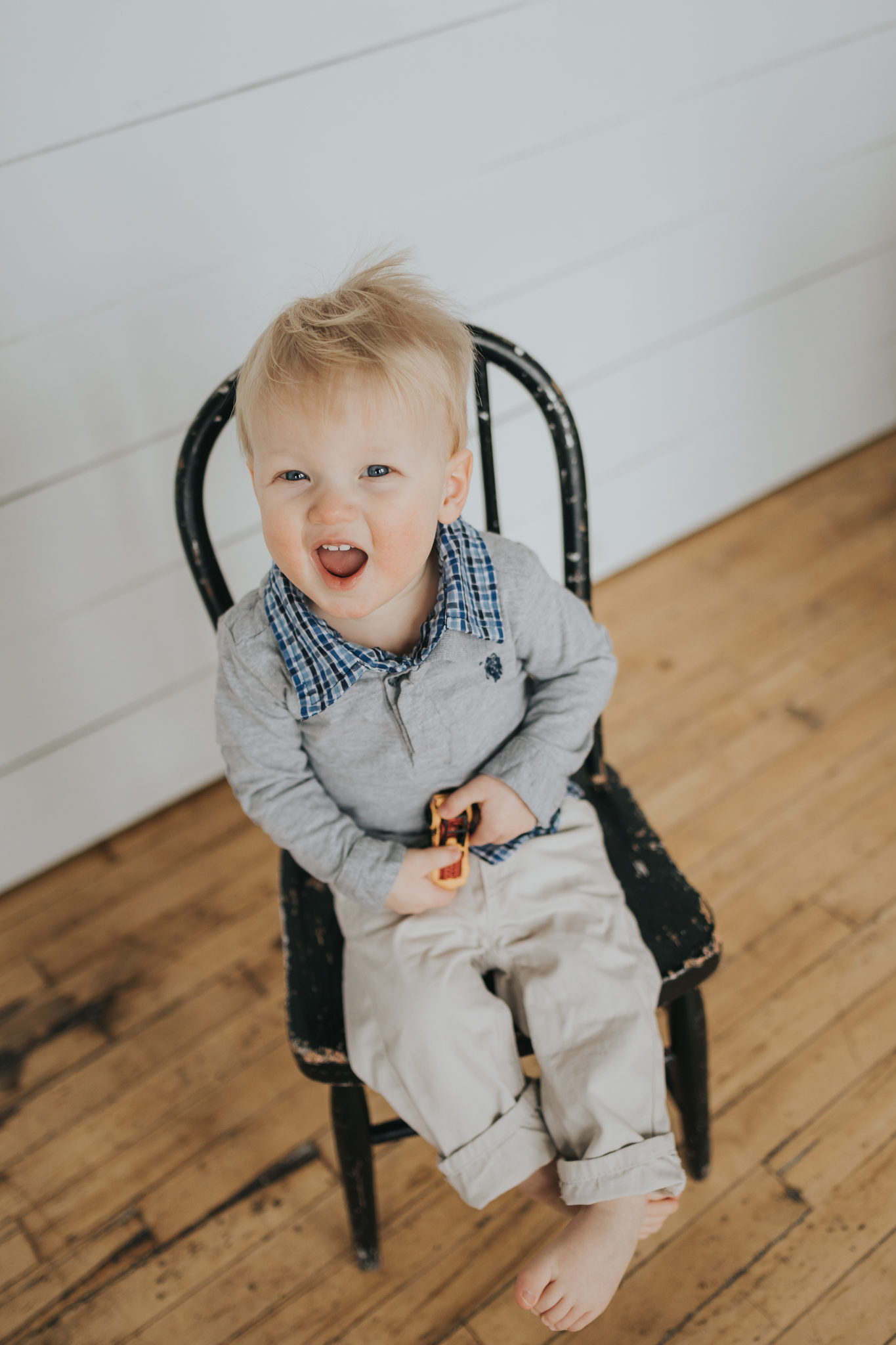 blonde one year old boy sitting in black chair holding yellow car - Minneapolis baby photgrapher