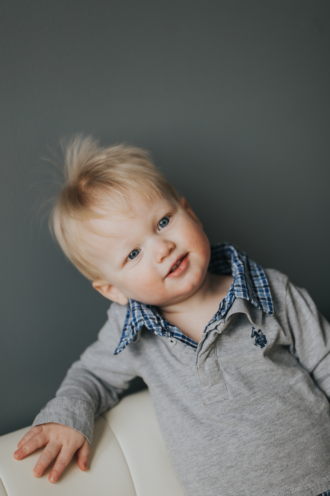 little boy with blonde hair standing on white couch - Minnesota Baby Photographer