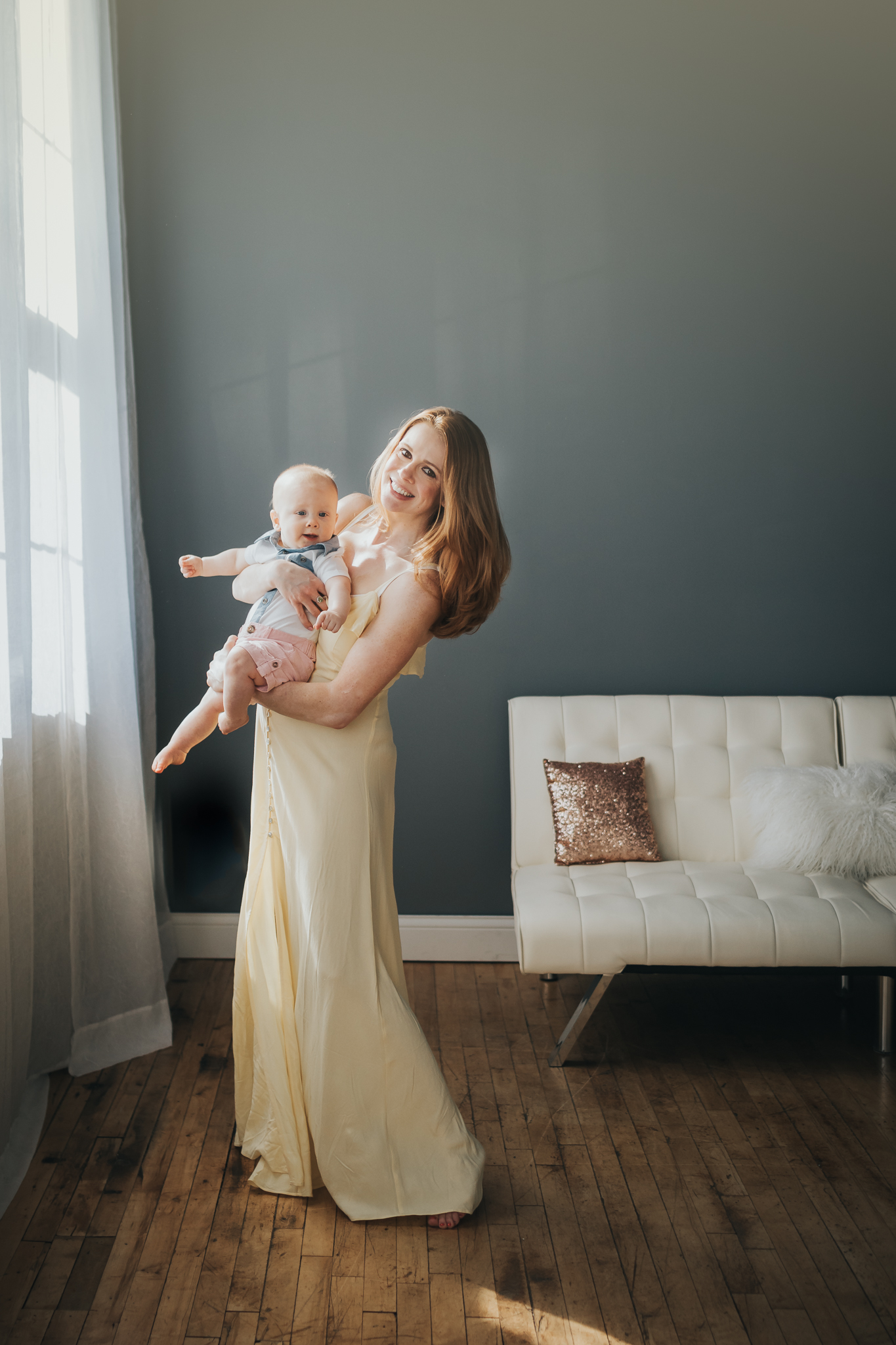mommy holding baby by window in blue room - Minneapolis Baby Photographer