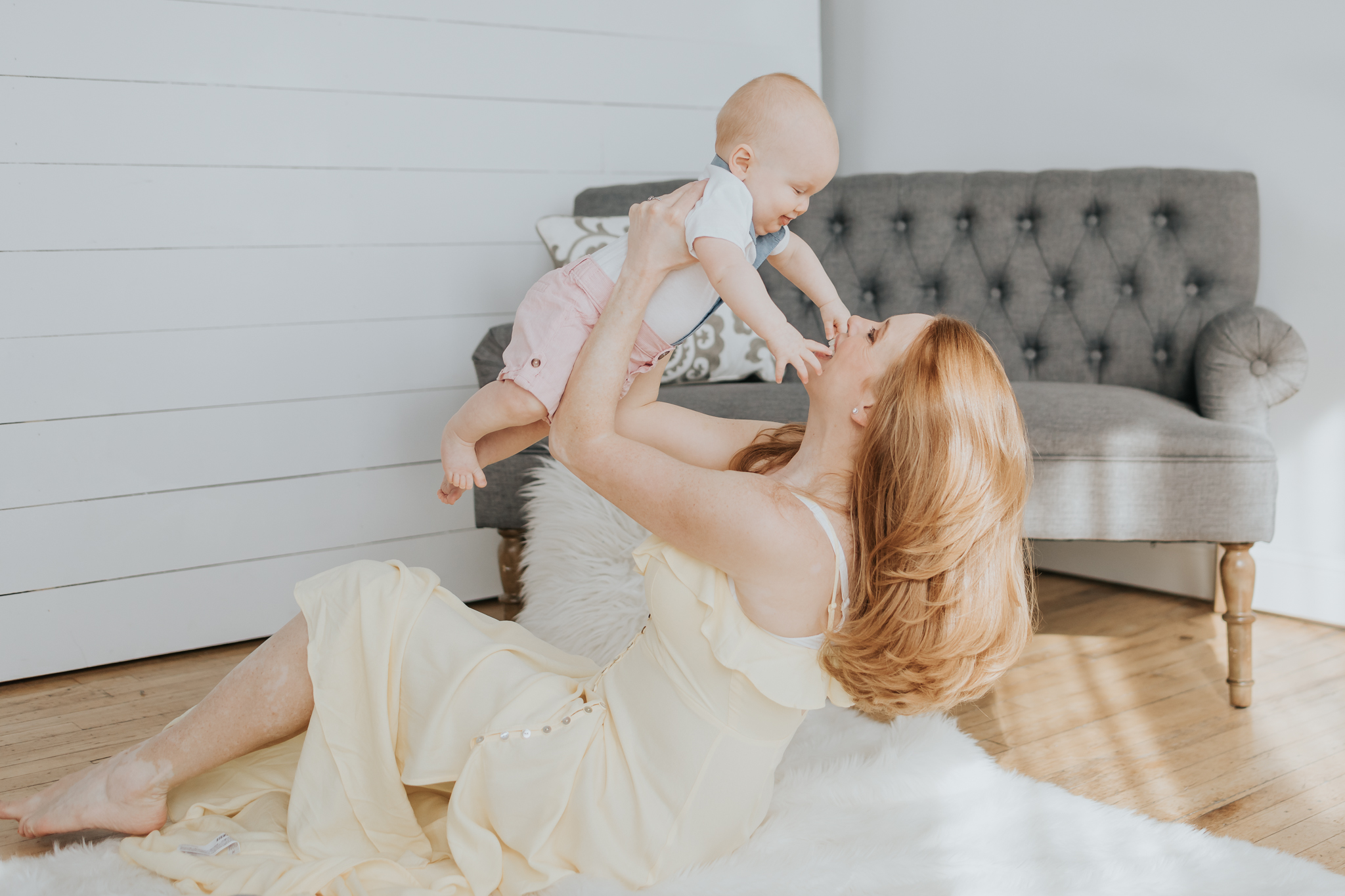 mom holding baby up and laughing next to a gray couch - Minneapolis Children's Photographer
