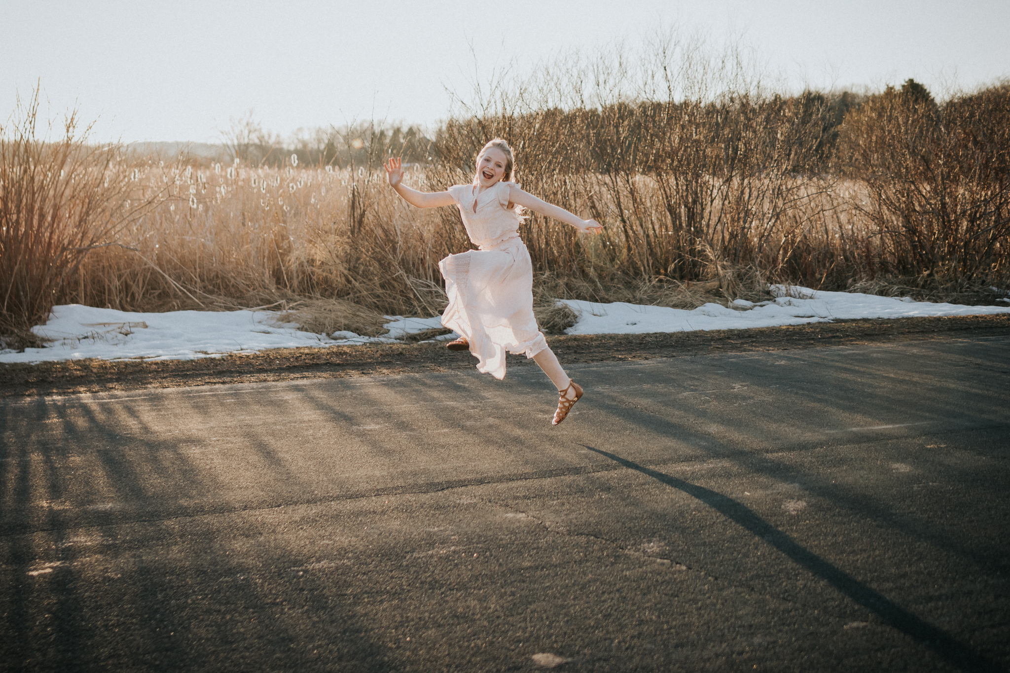 teenage girl leaping down a road - Minnetonka Family Photographer