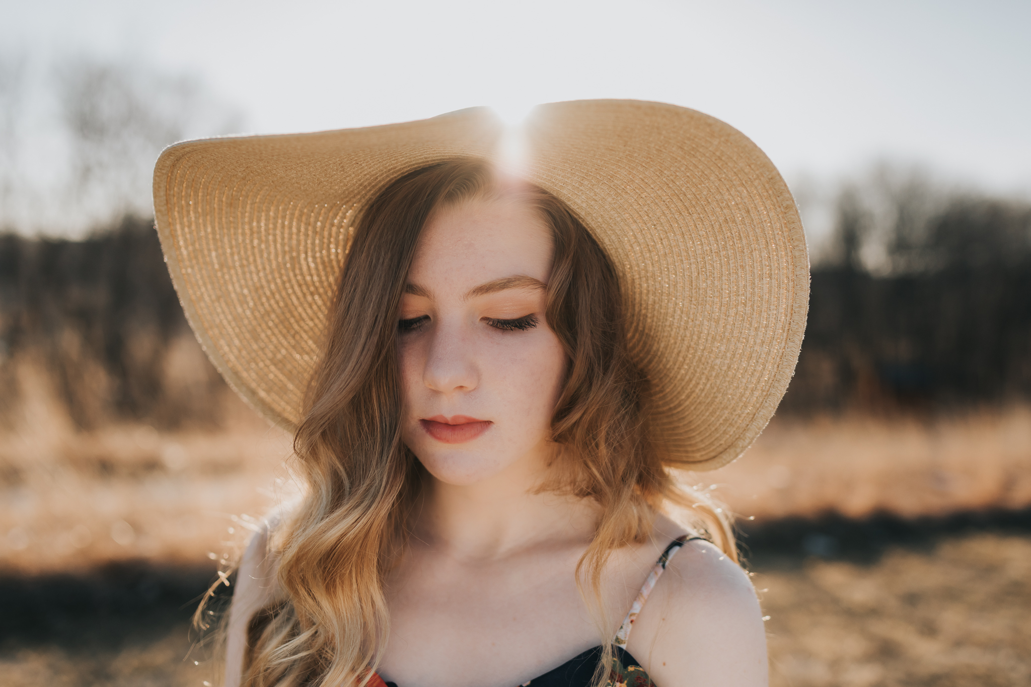 teenager girl wearing a hat with the sun shining through it - Twin Cities Senior Photographer