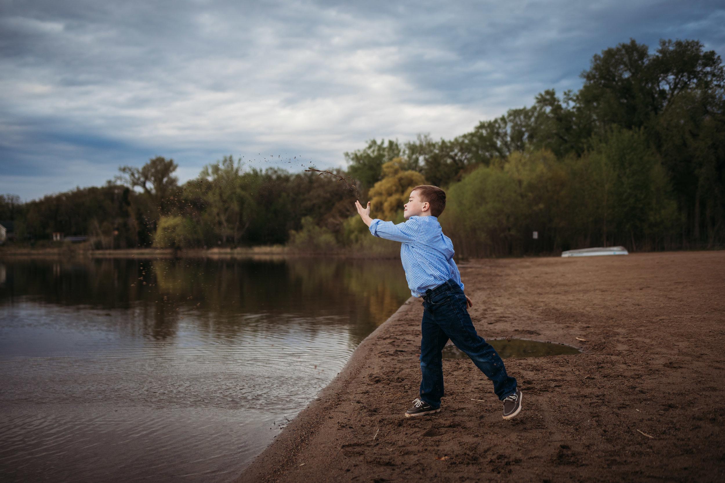 boy throwing rock into lake - Minneapolis Family Photographer