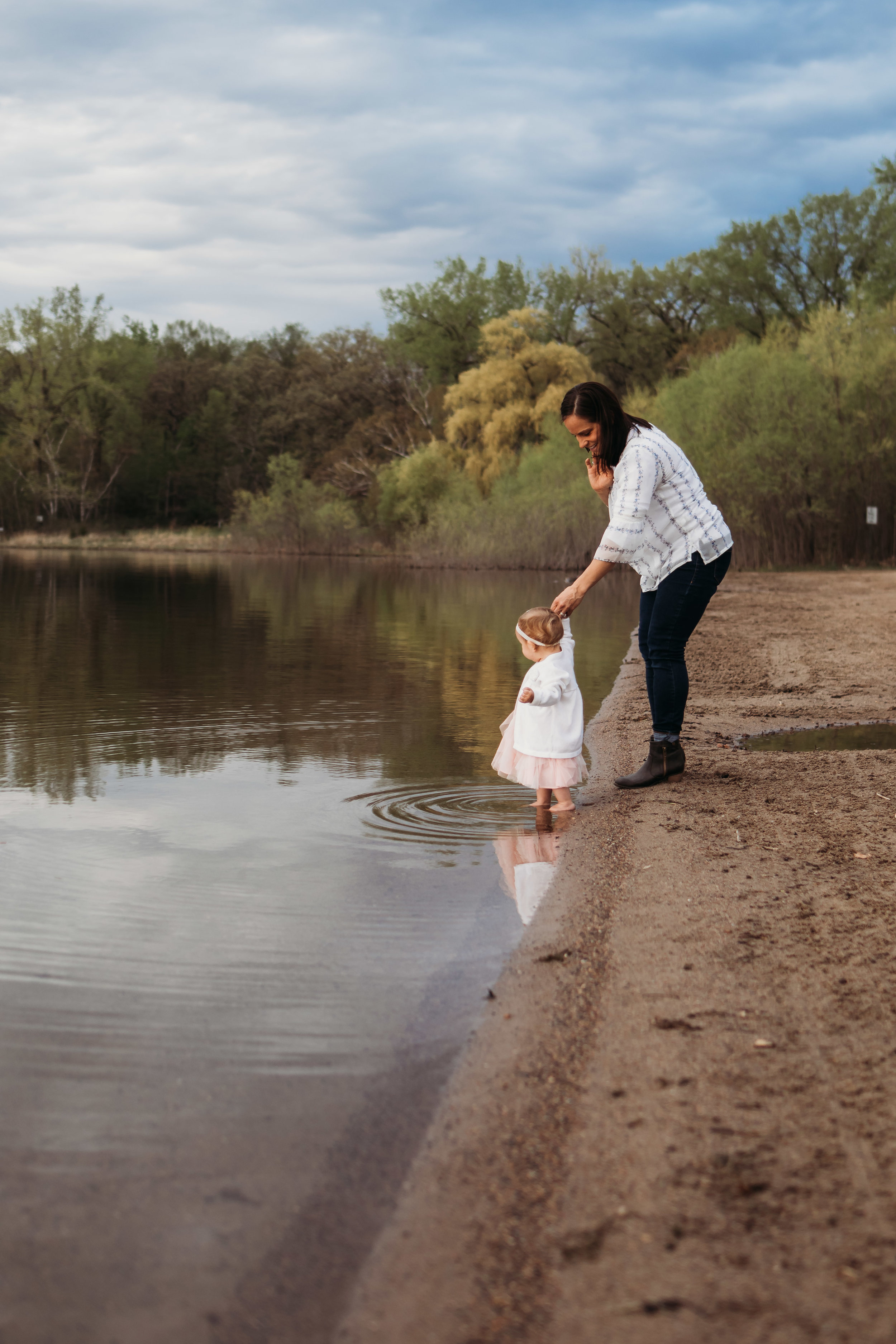 baby girl in pink walking in the water of lake - AMG Photography