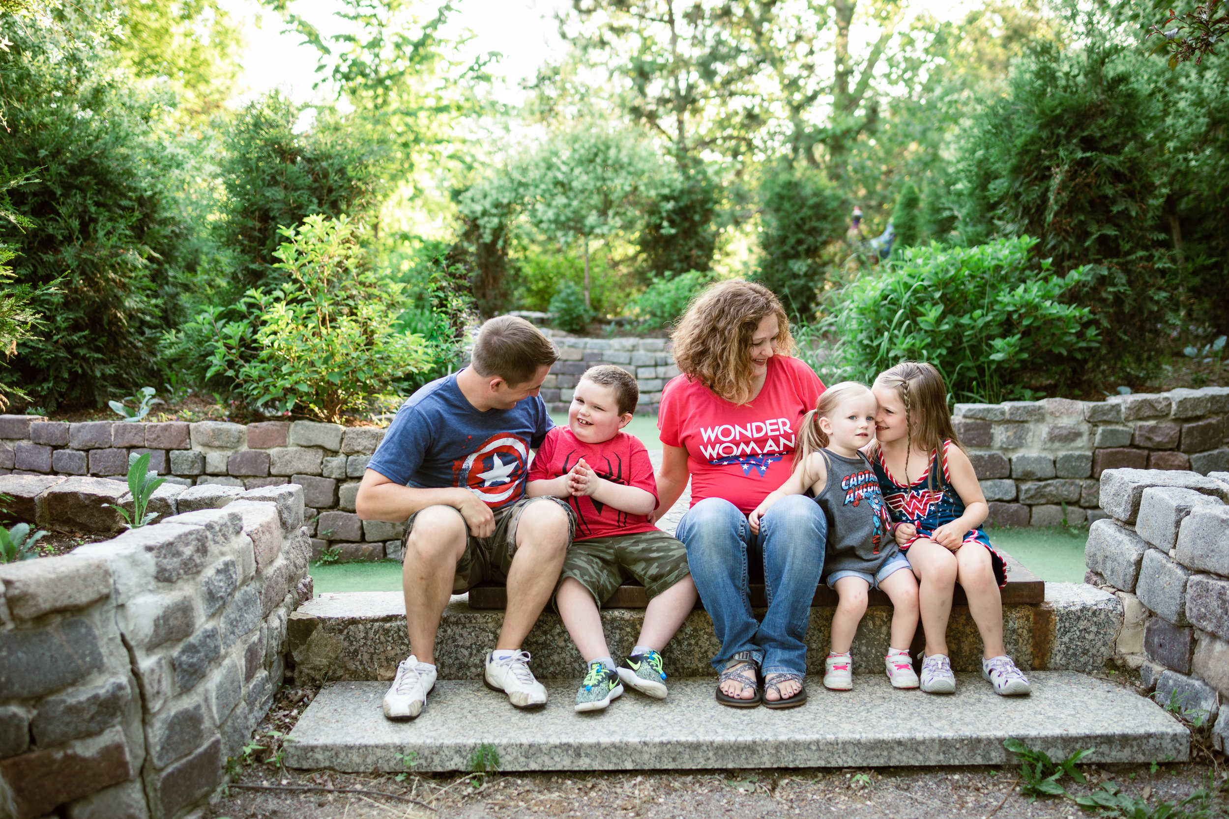 Family in super hero t-shirts sitting and talking - Minnesota Family Photographer