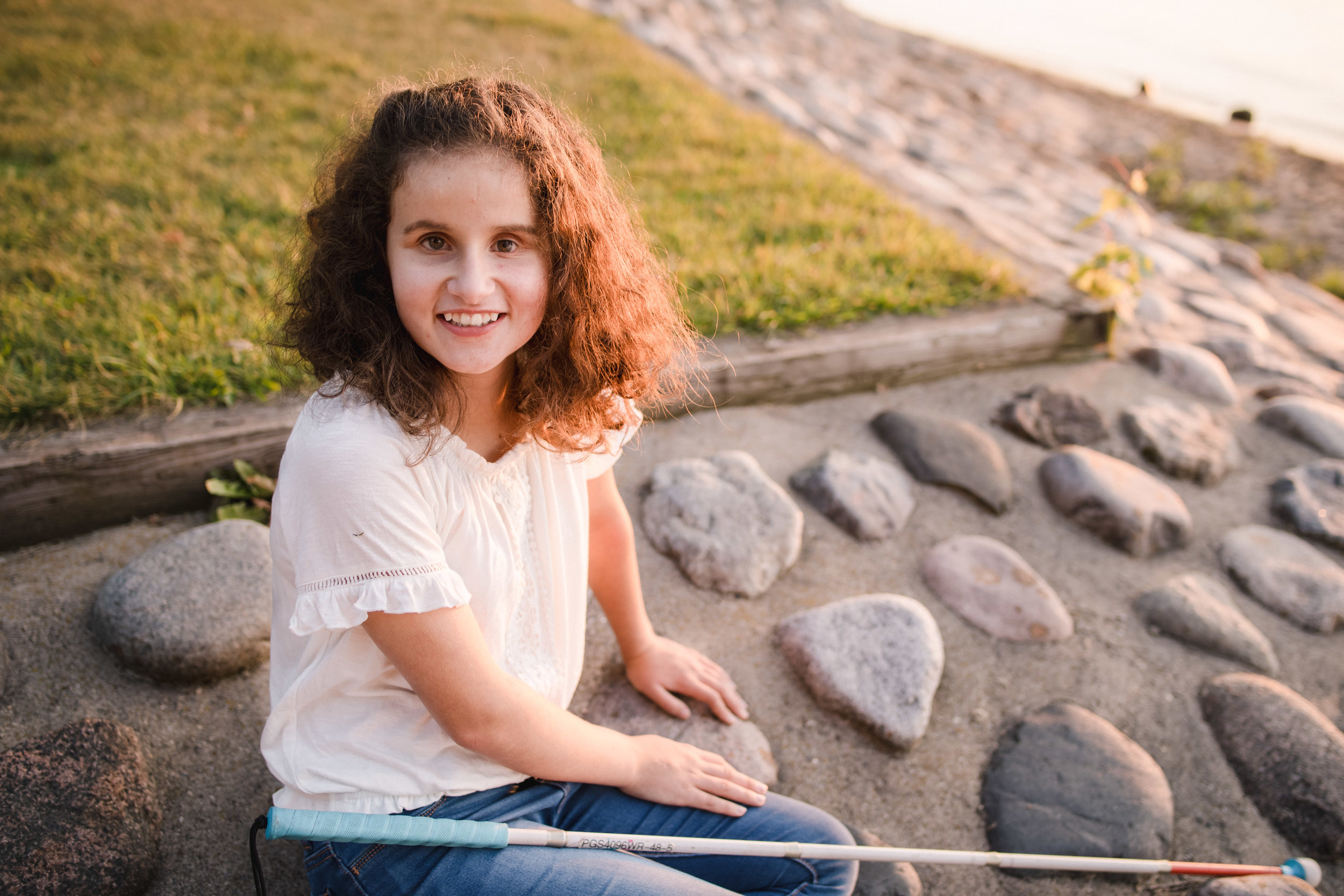 blind girl sitting on a beach by lake at sunset - Minneapolis Family Photographer