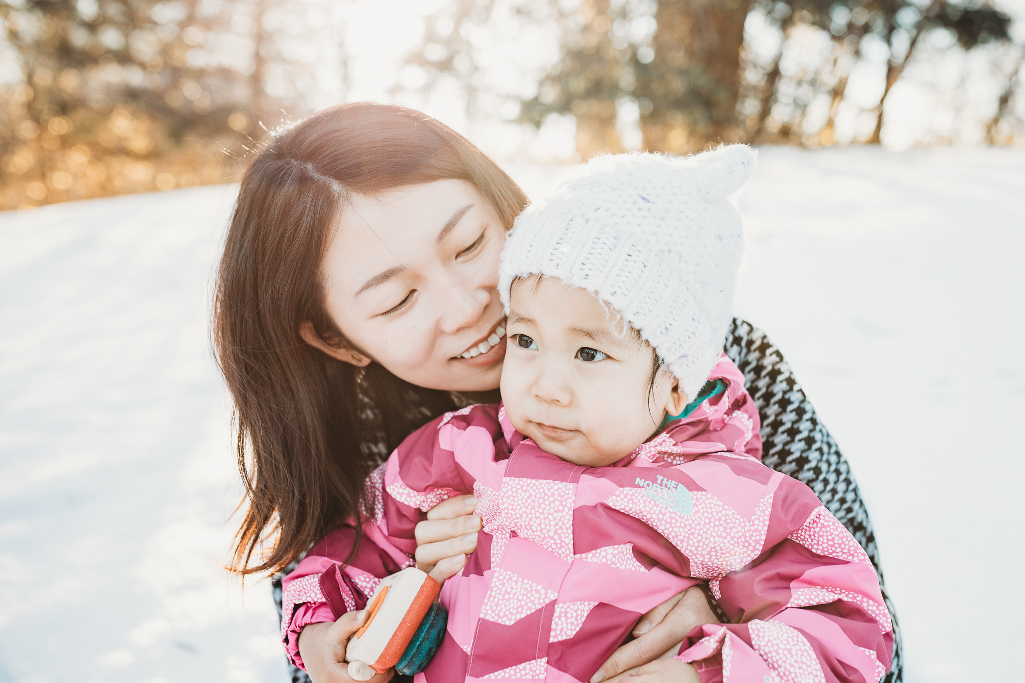 mom cuddling next to 2 year old daughter wearing pink in the snow - Minneapolis Family Photographer