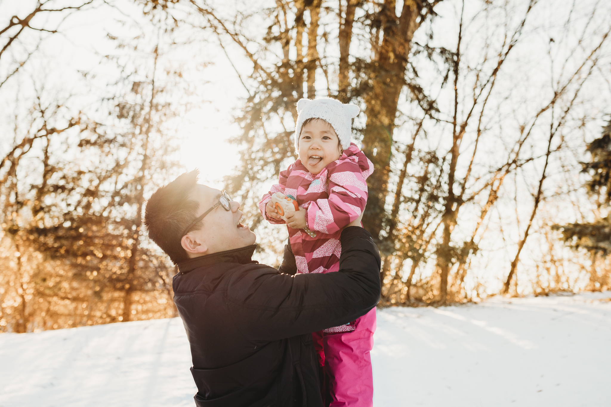 daddy holding baby girl up in the sky during winter - Minnesota family photographer