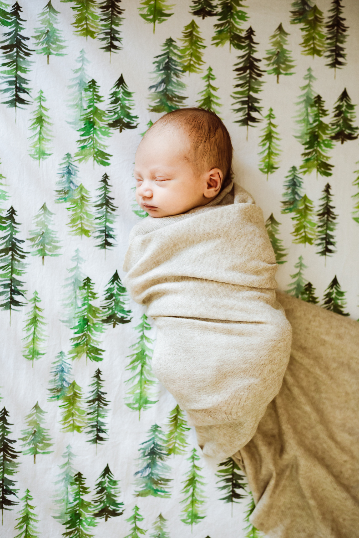 baby boy wrapped in a linen cloth sleeping in a crib  - AMG Photography